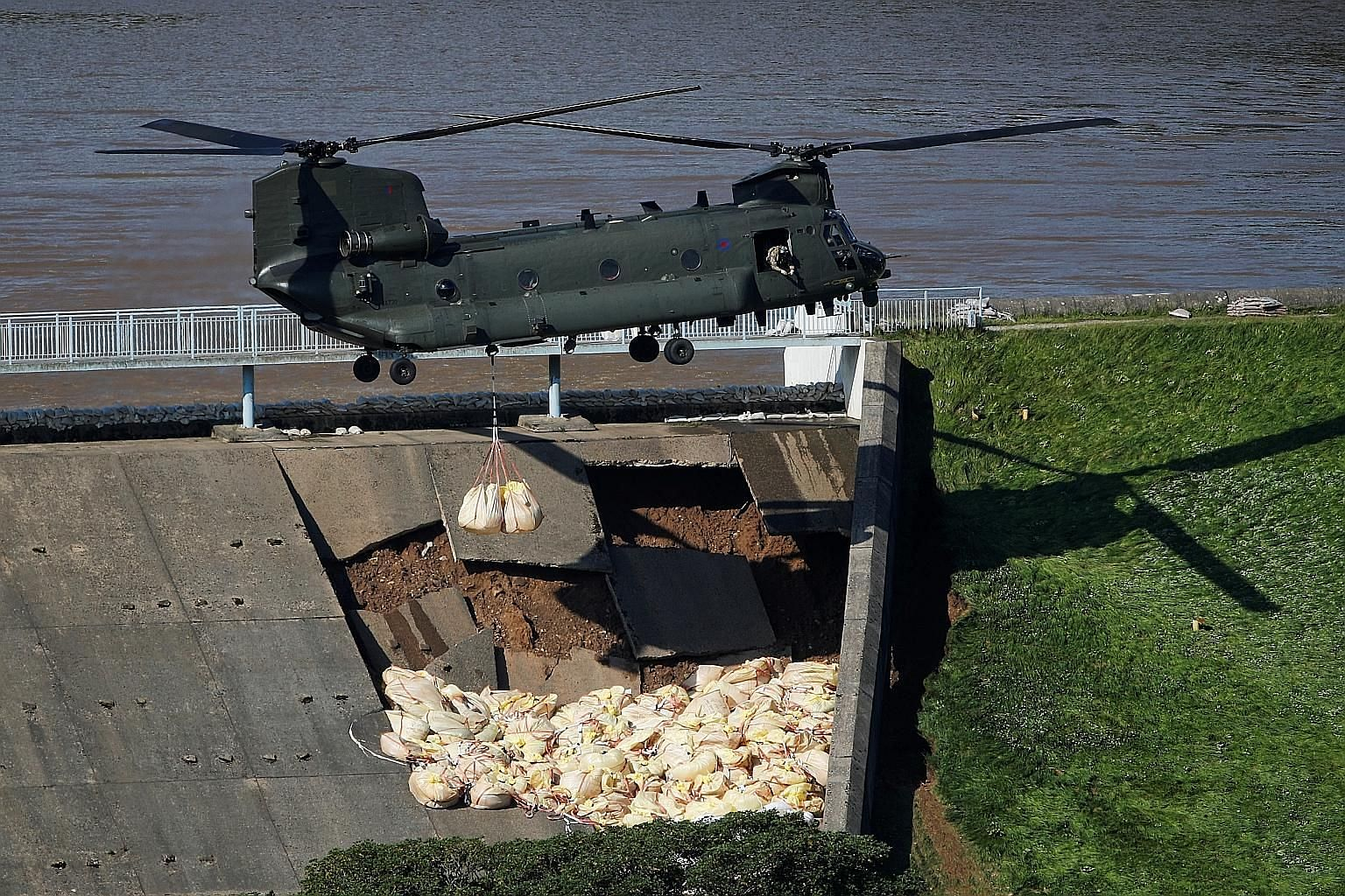 A Chinook helicopter dropping sandbags on top of the dam in Whaley Bridge in England yesterday. Officials said the dam, holding back 300 million gallons of water in the reservoir above the town, was in danger of failing.