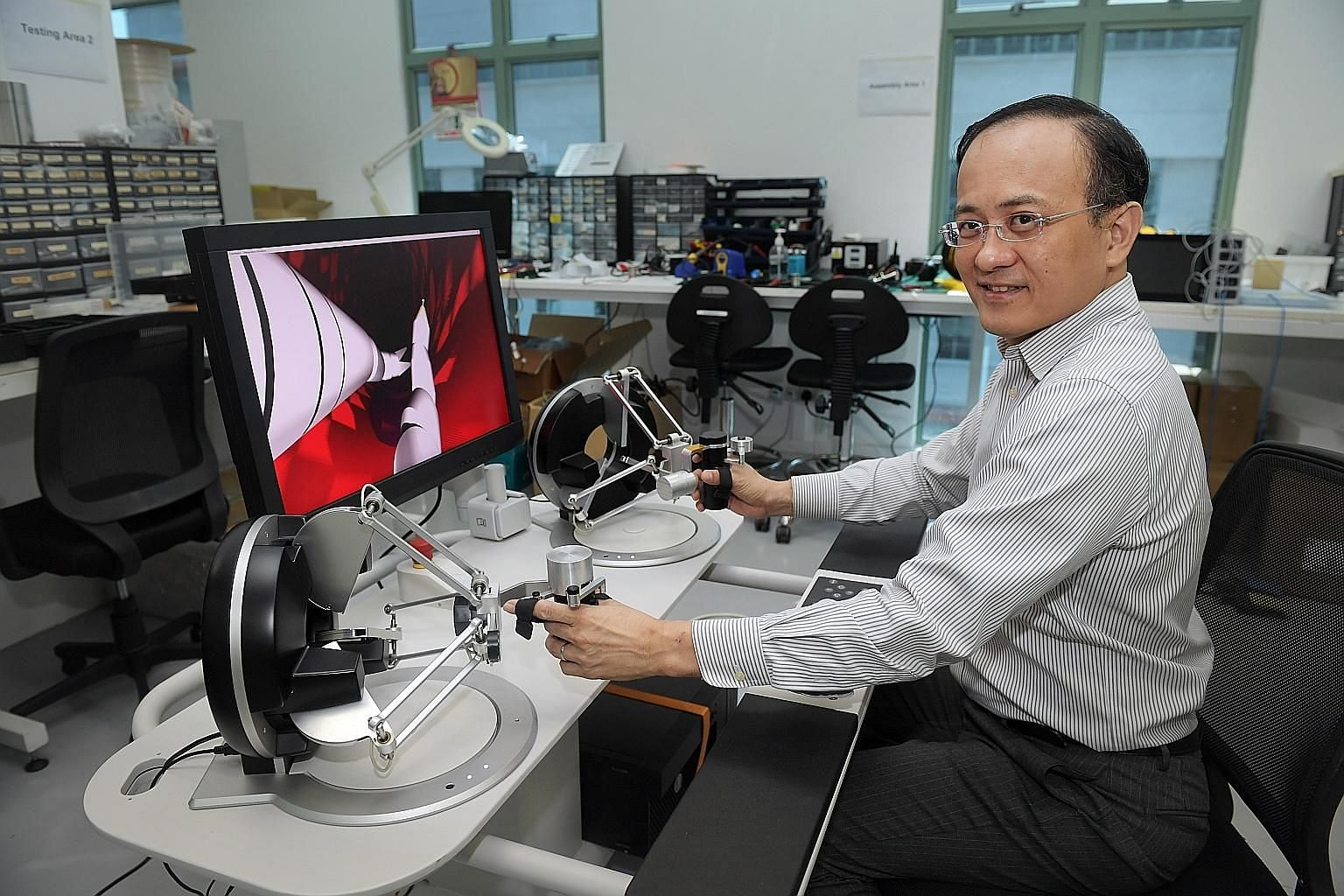Above: Biobot Surgical chief executive Sim Kok Hwee with a robotic system that can conduct prostate biopsies. The system, developed with Singapore General Hospital, is being used in Singapore hospitals and in Australia and Europe. Left: EndoMaster ch