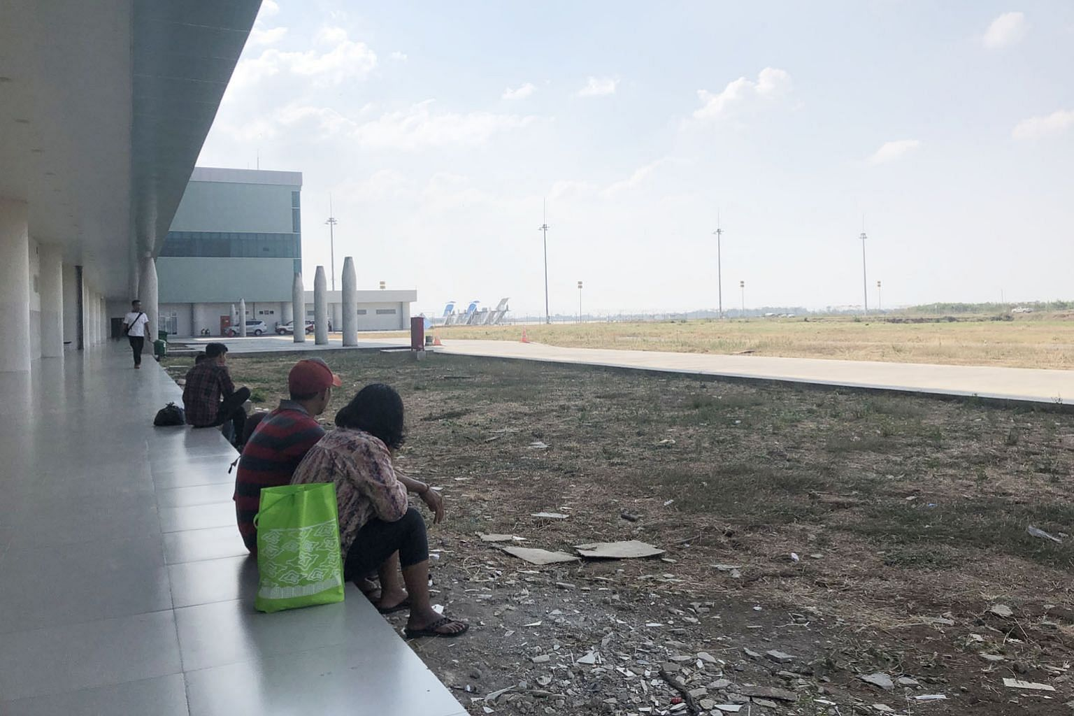 Mr Idris Ridha and his family waiting for their flight at Kertajati International Airport. The trio missed the free shuttle bus from Bandung to Kertajati and had to hire private transport with five other travellers to get to the airport. Travellers s