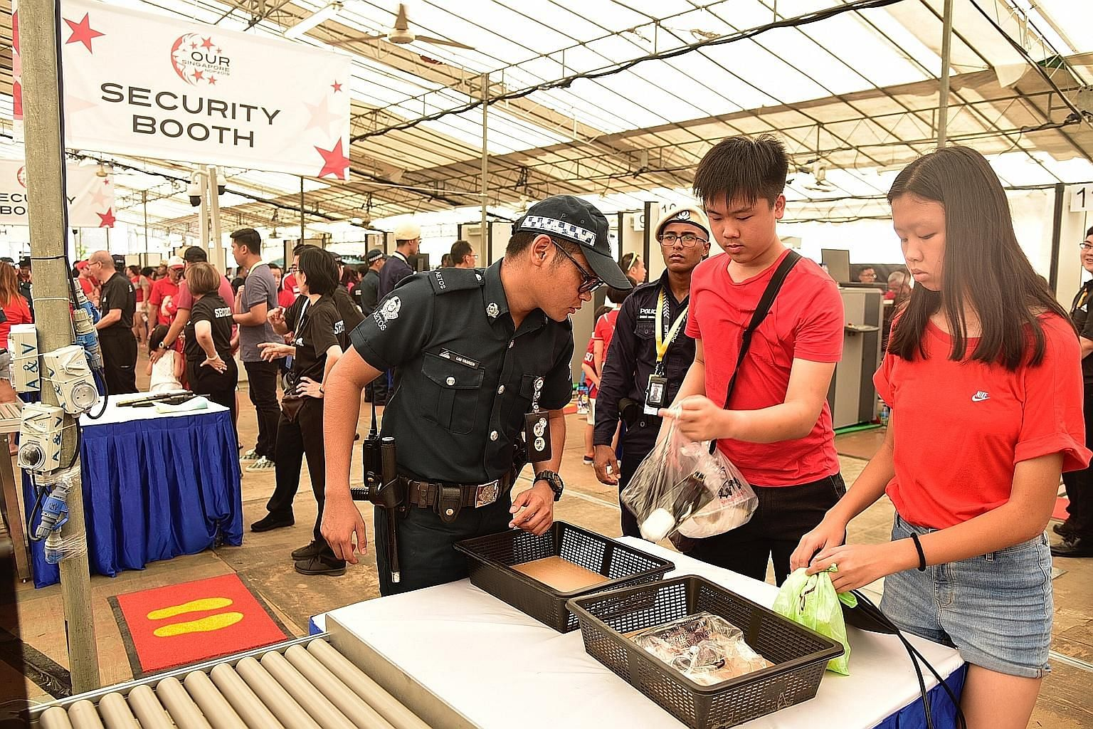 People attending this year's National Day Parade preview at the Padang yesterday having their belongings checked. Security checks will be carried out on everyone entering the venue, including using walk-through metal detectors. Personal belongings wi