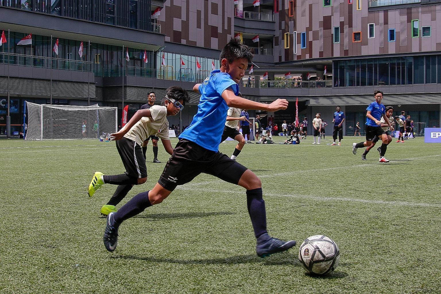ActiveSG Football Academy Serangoon Development Centre's Under-13 side (in blue) taking on AFA Toa Payoh DC at Our Tampines Hub yesterday in the Epson Youth Challenge.