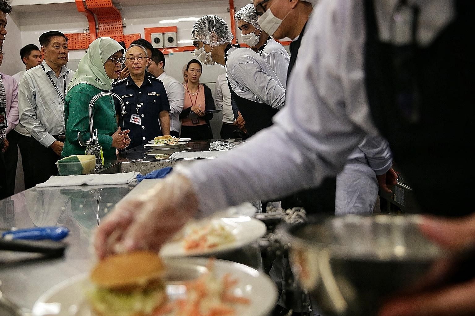 President Halimah Yacob interacting with inmates during her visit to the Hope Cafe, a training kitchen and restaurant in Changi Prison Complex where inmates undergo hands-on training in culinary skills and food and beverage operations - to enable the