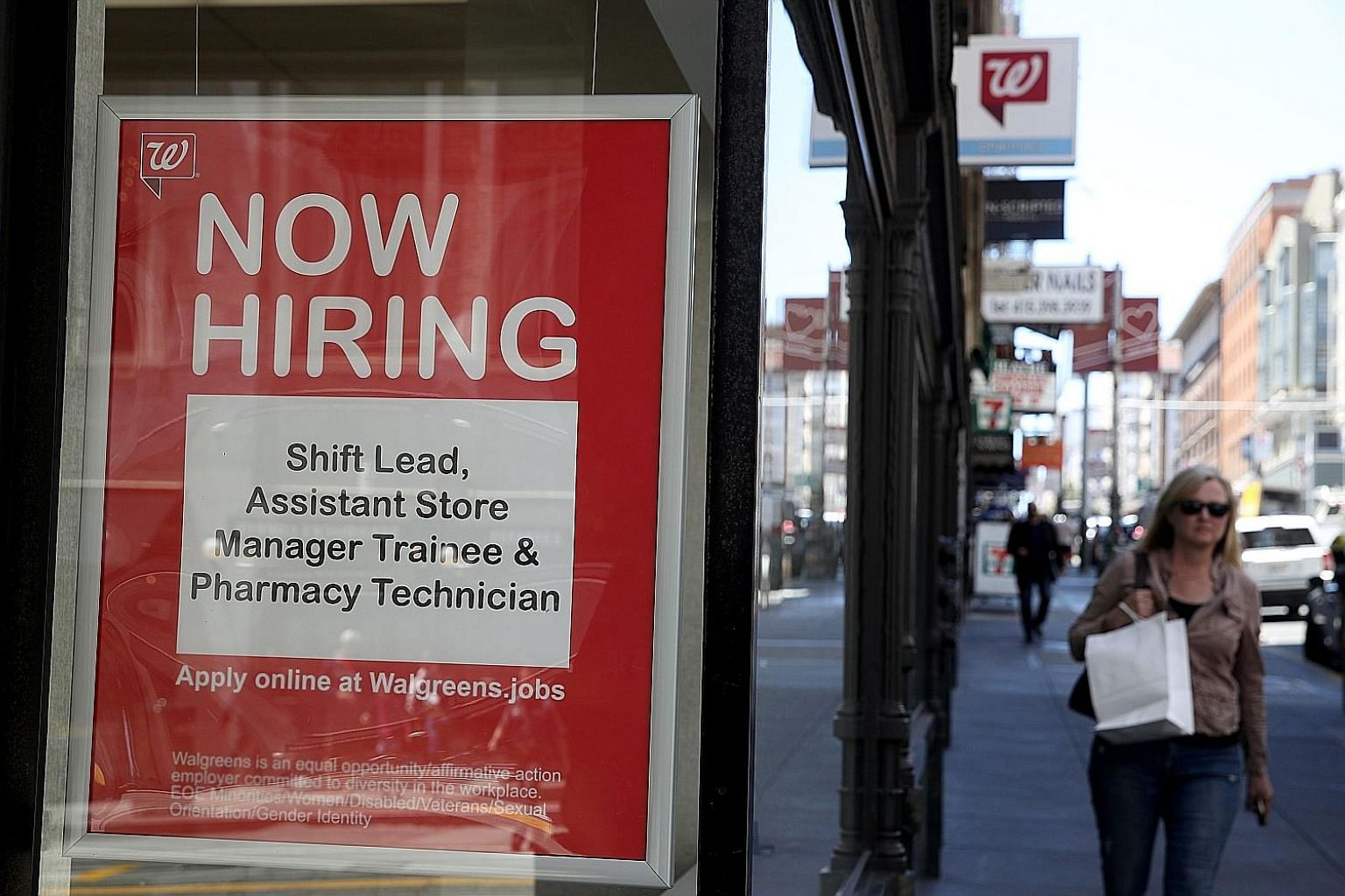 A job-hiring sign posted on the window of a Walgreens store in San Francisco, California. According to the writer, a labour market in which workers can support strong families and communities is the central determinant of long-term prosperity and sho