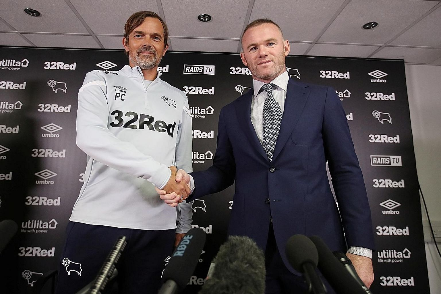 Derby County manager Phillip Cocu (far left) and his prized recruit Wayne Rooney pose during the press conference to unveil the former England and Manchester United star on Tuesday. PHOTO: REUTERS