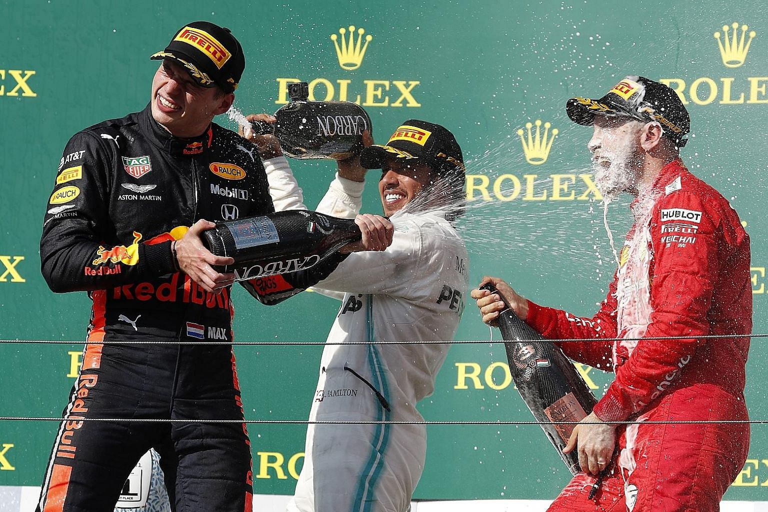 Ferrari's Sebastian Vettel (right) is not a happy man after finishing third in the Hungarian Grand Prix behind Mercedes' Lewis Hamilton (centre) and Red Bull's Max Verstappen. Vettel has underperformed this season after excelling in testing - falling