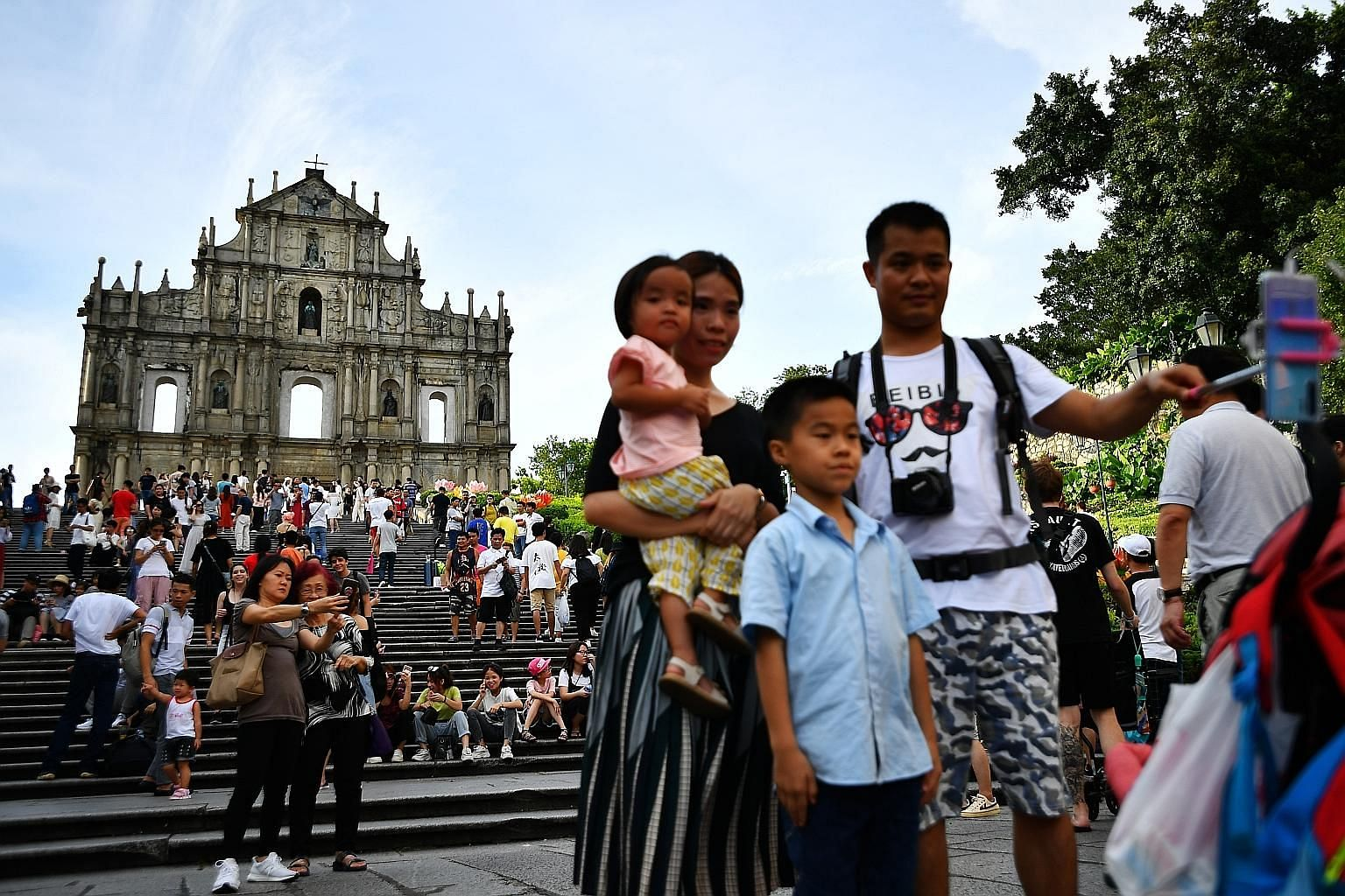 Tourists at the Ruins of St Paul's, officially listed as part of the Historic Centre of Macau, a Unesco World Heritage Site. Many visitors are steering clear of the world's biggest gambling hub, worried over transport disruptions and safety concerns
