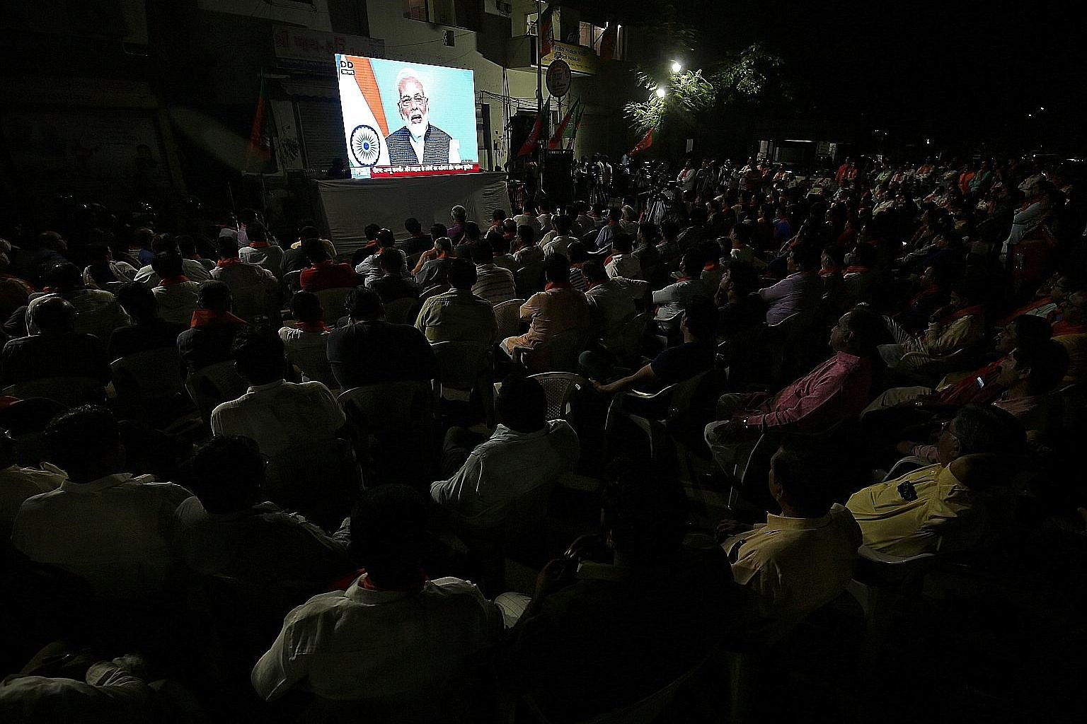 People watching a broadcast of Prime Minister Narendra Modi delivering his televised address to the nation in Ahmedabad, India, yesterday. The decision to withdraw Jammu and Kashmir's special status and bifurcate the state has had domestic and intern