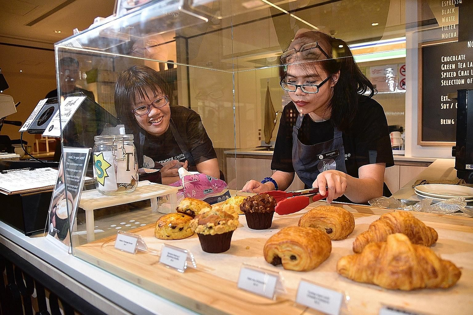 The Special Employment Credit scheme offers a monthly wage subsidy of about $200 to employers for every employee with a disability who is hired, like Ms Carmen Tan Yin Xin (left), 23, and Ms Rachael Lum Yuan Ting, 19, who work at Foreword Coffee. But