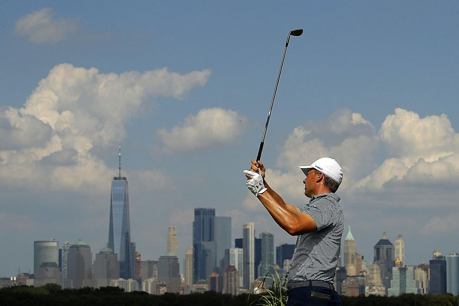 Jordan Spieth hitting off the 14th tee at The Northern Trust at Liberty National Golf Club in Jersey City on Thursday. he followed his opening four-under 67 with a 64 on Friday to head into the weekend in second place. PHOTO: AGENCE FRANCE-PRESSE