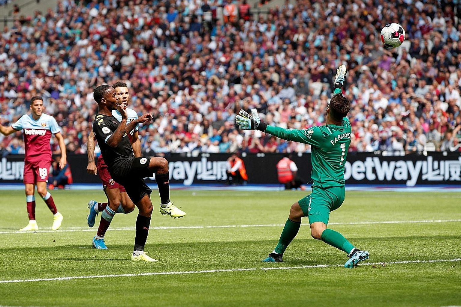 Raheem Sterling lobbing West Ham goalkeeper Lukasz Fabianski for Manchester City's third goal, and his second, at the London Stadium. The English forward later completed his hat-trick as the champions hit the Hammers for five in a one-sided league op