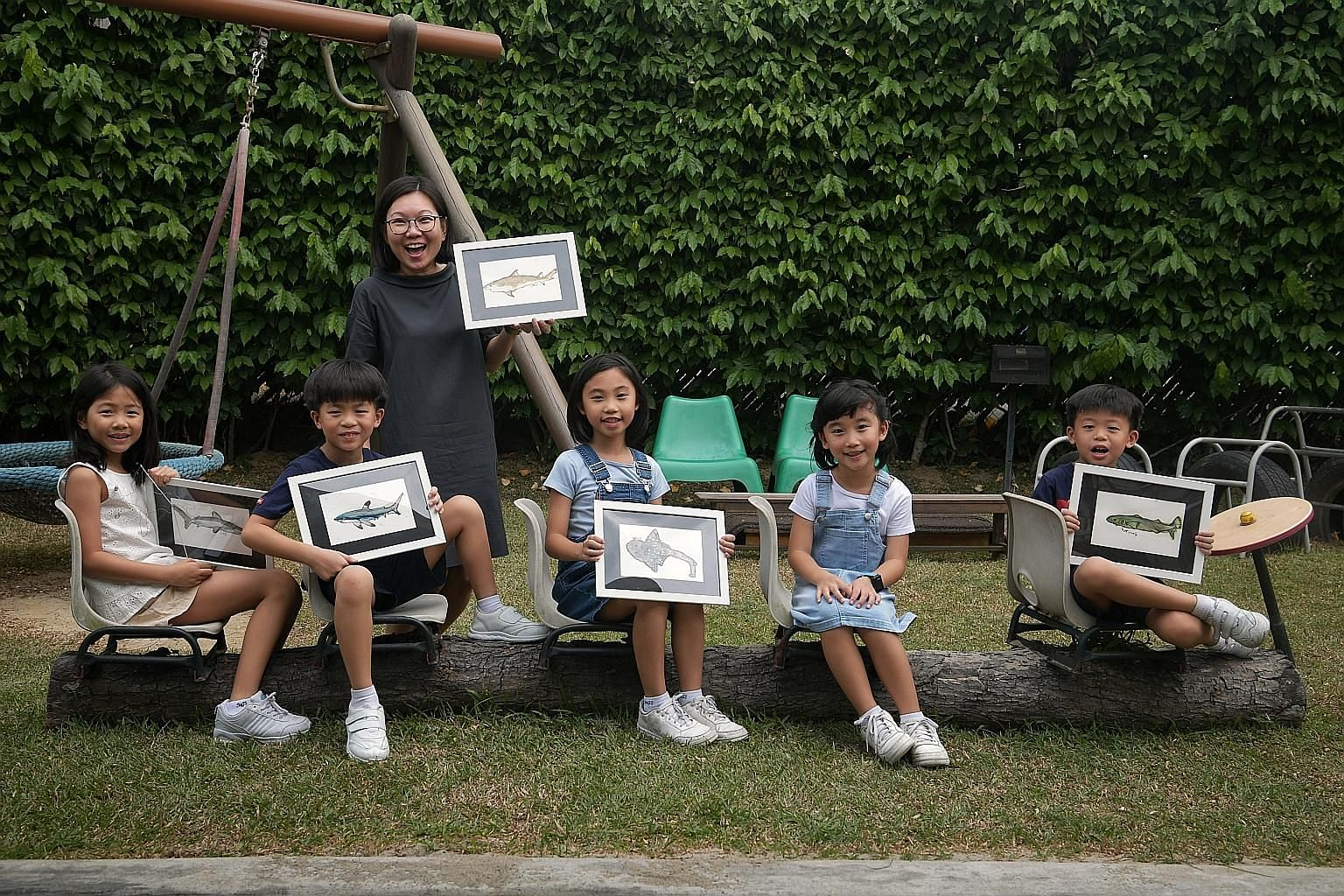 EtonHouse Pre-School senior teacher Wong Wei Sum with the children - (from left) Lily Huang, Liam Ong, Chloe Tan, Katie Tan and Lucius Ong - behind a video that was part of WWF-Singapore's anti-shark fin campaign on social media last year.