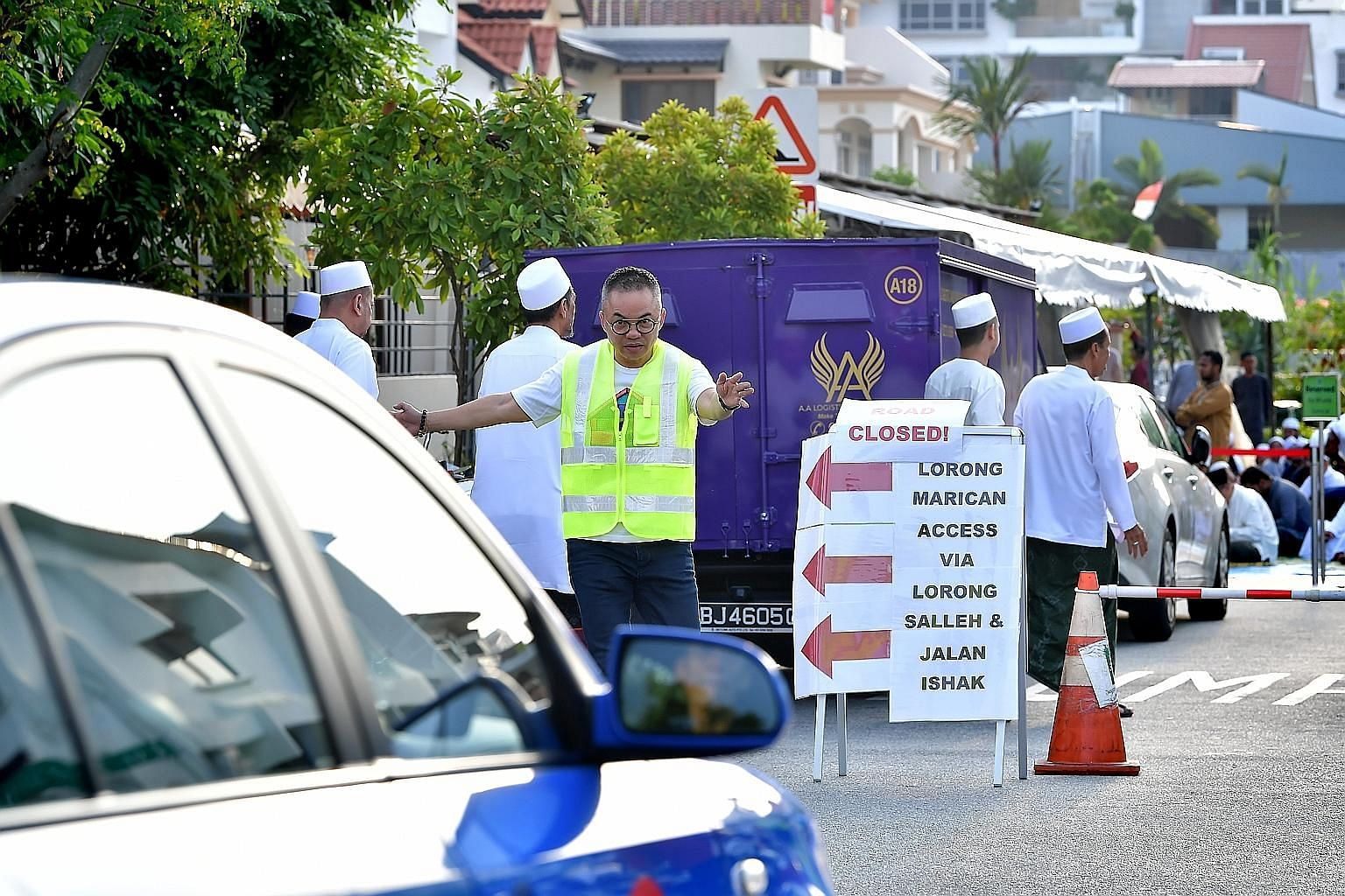 Congregants praying inside as well as outside Abdul Razak Mosque during yesterday morning's prayers. Mr Jacky Ho, 50, a volunteer from Buddhist organisation Shinnyo-en, helping to direct traffic as more than 1,000 Muslims gathered at Abdul Razak Mosq