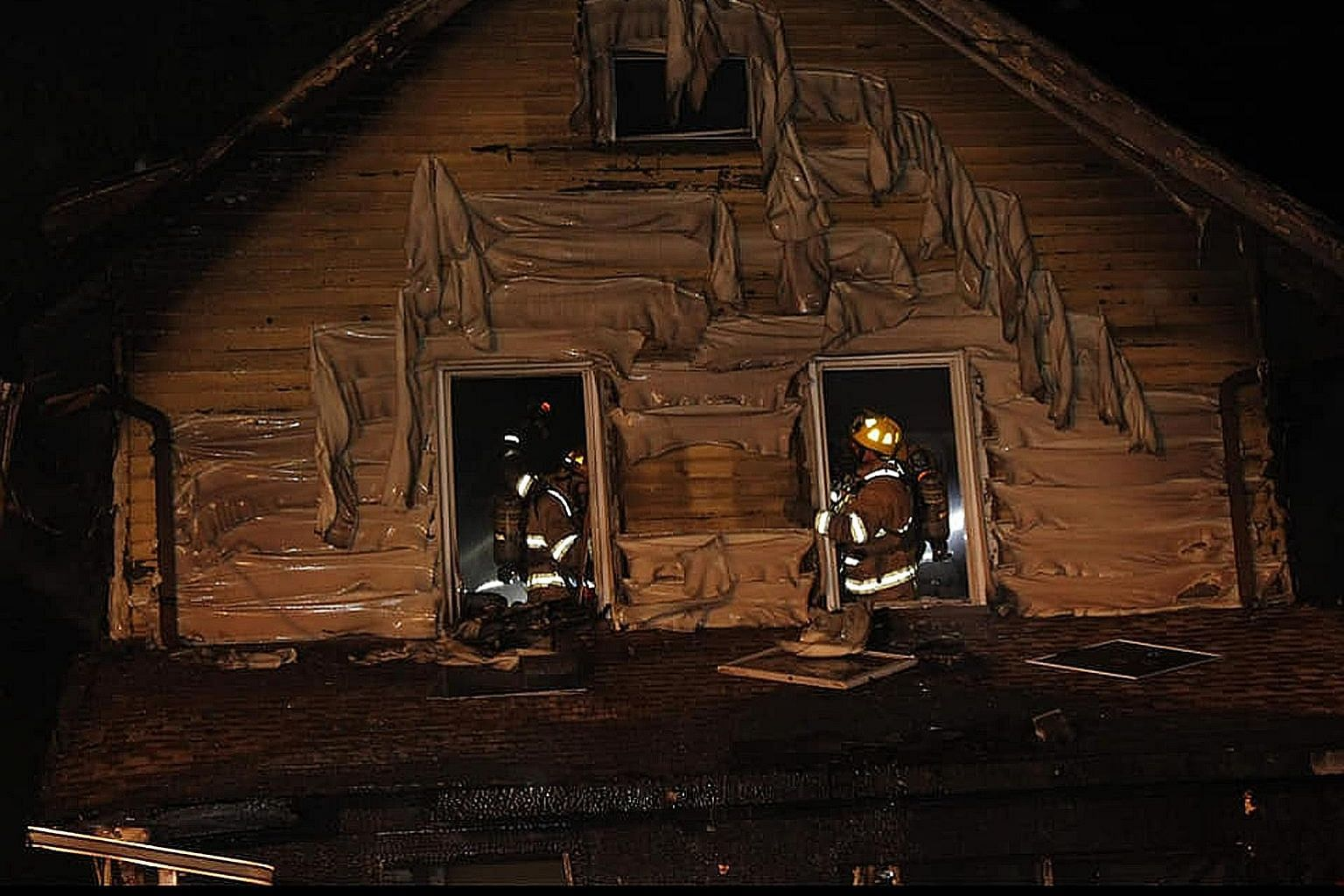"""Firefighters at the daycare centre in Erie, Pennsylvania, on Sunday. The US city's fire chief said the five children, aged eight months to seven years, were sleeping in second-floor bedrooms when the blaze broke out. He said investigators were """"leani"""