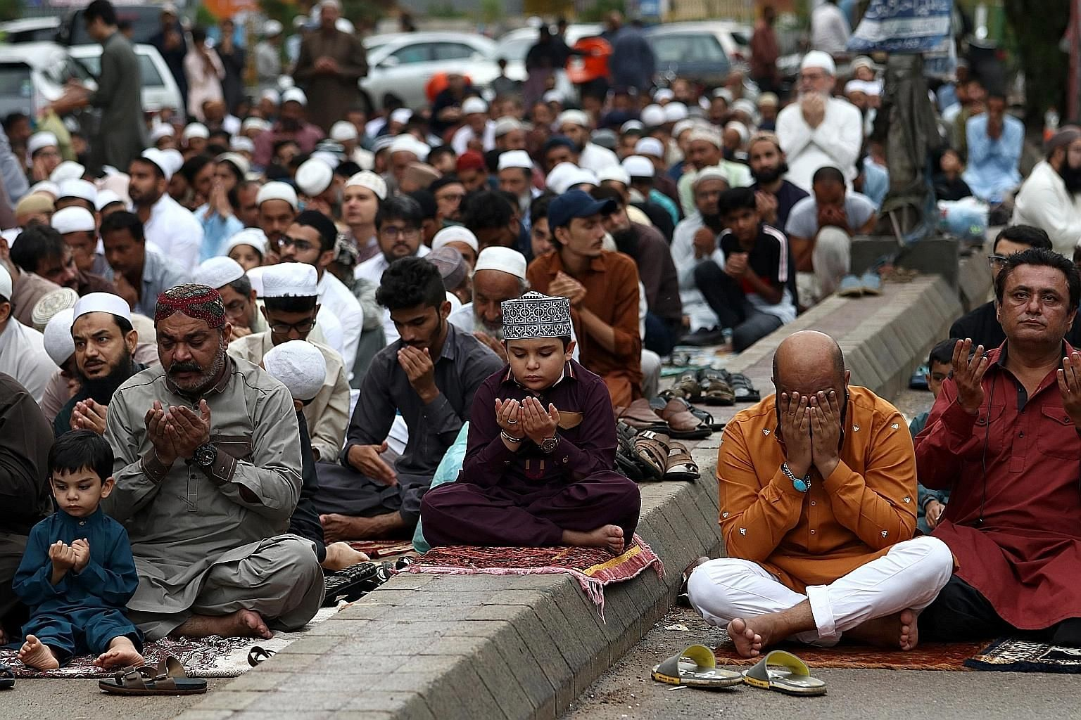 """People praying during Eid al-Adha in Karachi yesterday. Islamabad has called for the festival to be observed in a """"simple manner"""", to express solidarity with Kashmiris living on the Indian side of the divided region. PHOTO: EPA-EFE"""