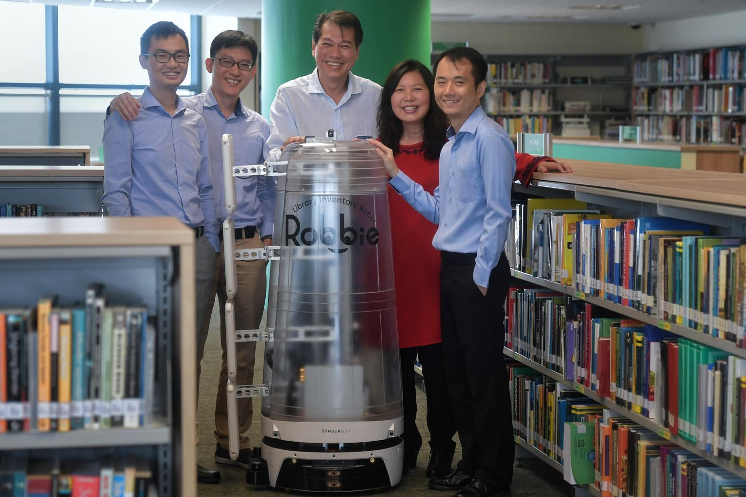 Senserbot team members (from left) vice-president for research and development Li Renjun, chief technology officer Ho Chin Keong and chief executive Peter Mao, with Temasek Polytechnic's library director Puspa Yeow and librarian Tan Han Yong. Robbie's cas