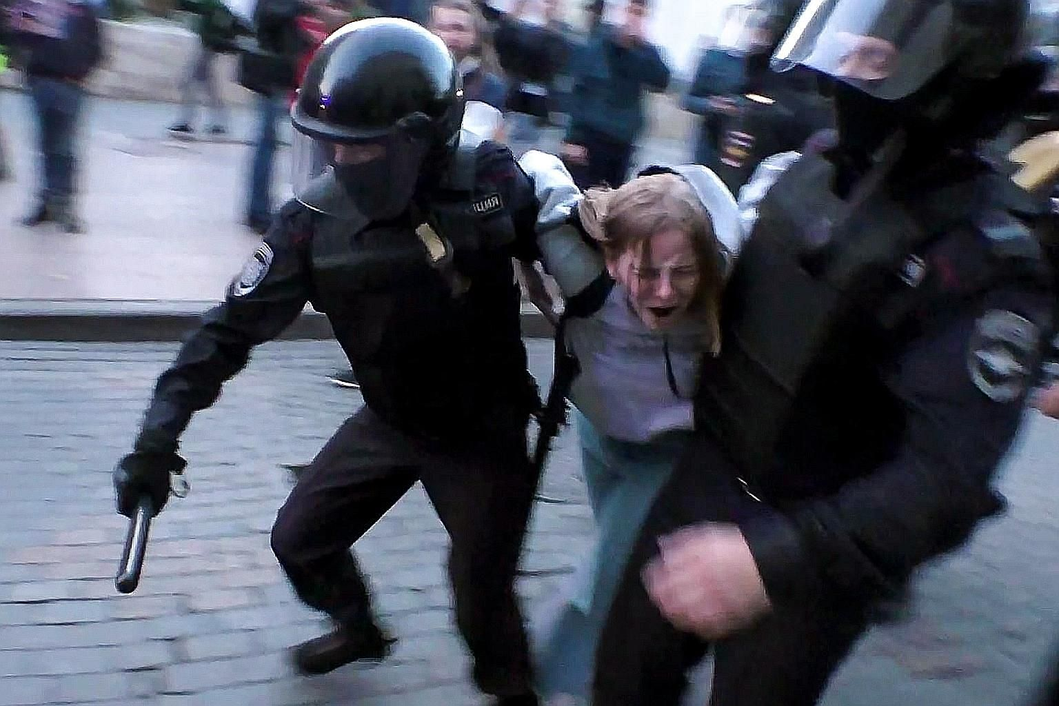 """Russian riot police detaining a protester after a rally for fair polls in Moscow last Saturday. The protests were triggered by the mass """"barring"""" of opposition candidates who wanted to take part in the elections."""