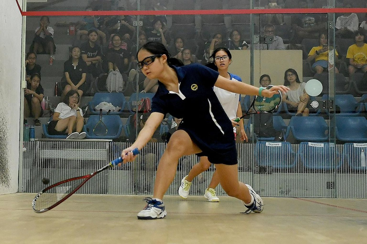 Methodist Girls' School's Gracia Chua (in blue) hitting a return during her win over National Junior College's Ong Rui En in the C Division squash final at Kallang Squash Centre. ST PHOTO: KHALID BABA