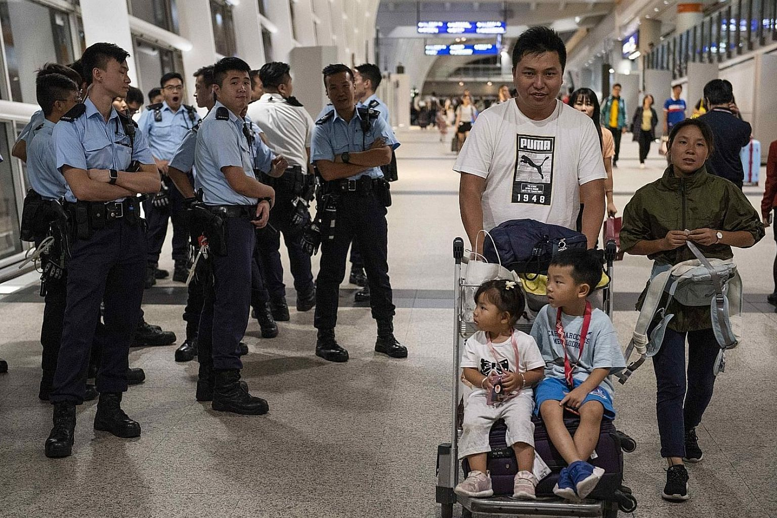 Police protecting passengers at the Hong Kong airport on Wednesday as flights resumed. Sentiment on the ground appears to be turning in favour of the government. PHOTO: DPA