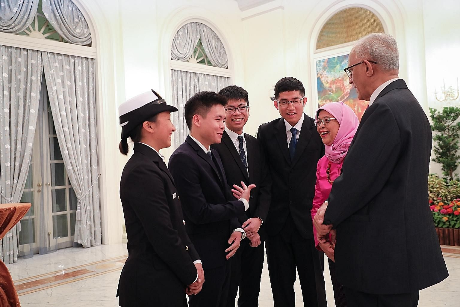 President Halimah Yacob and her husband, Mr Mohamed Abdullah Alhabshee, with this year's President's Scholarship recipients (from far left) Allison Tan Sue Min; Siow Mein Yeak, Yue; John Chua Je En; and Muhammad Dhafer Muhammad Faishal at the Istana