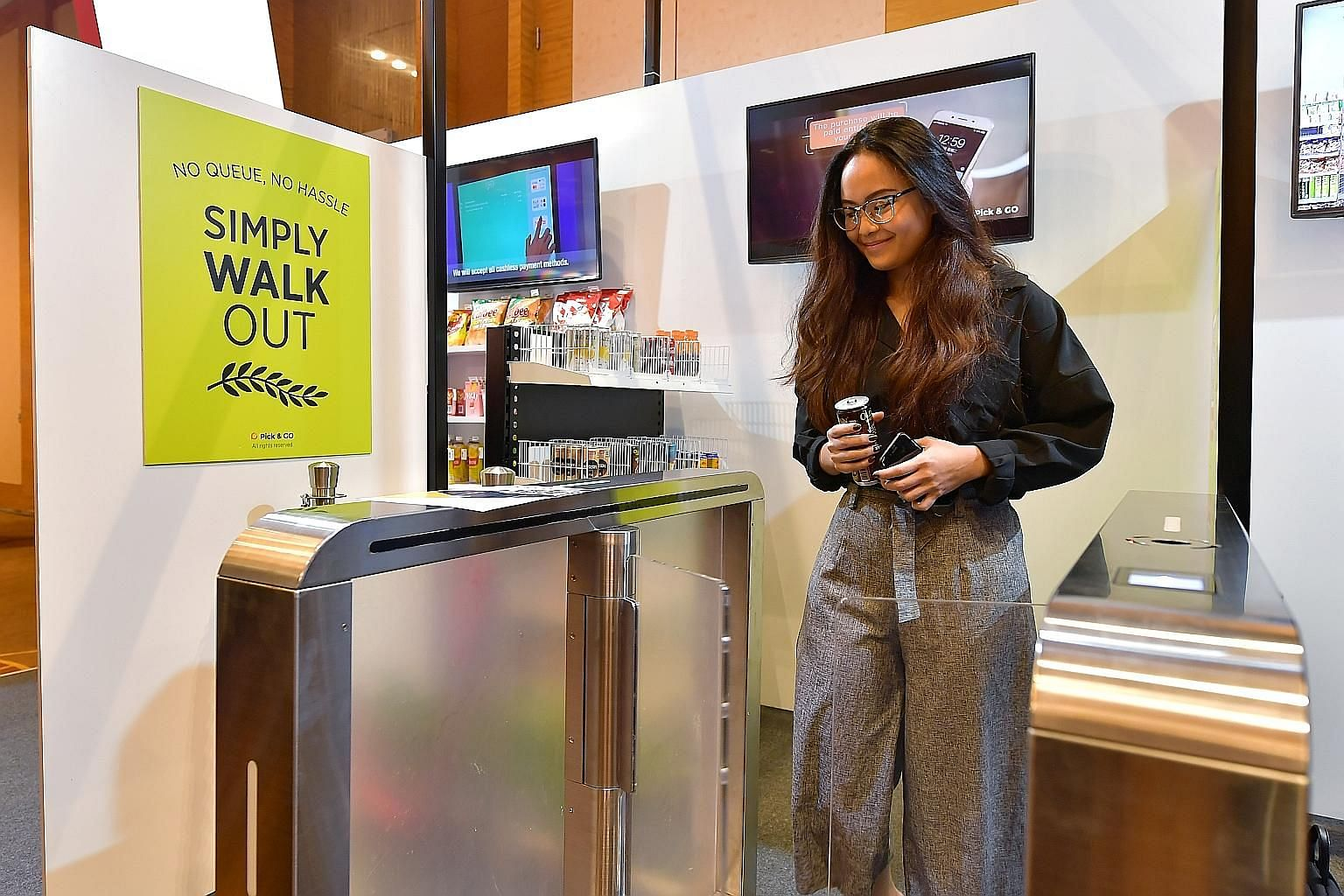 A guest at the Singapore Retail Industry Conference and Exhibition 2019 using an unmanned booth by Pick & Go. The booth eliminates the need for cashiers, with shoppers paying for their purchases by tapping in and out of gateways.