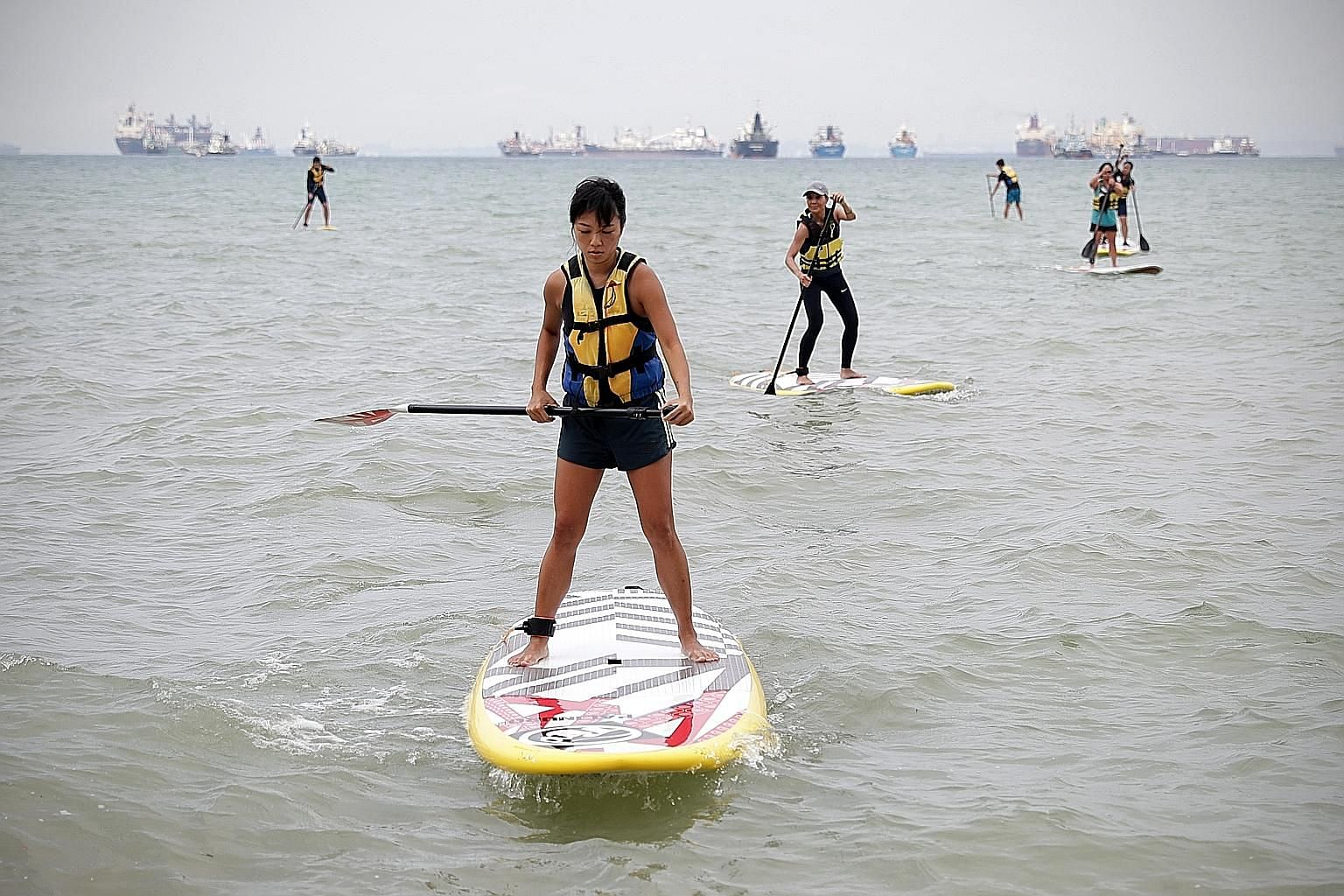 Ms Jessica Wee (foreground) heading back to shore after a session with the stand-up paddling interest group at East Coast Park. ST PHOTO: NEO XIAOBIN