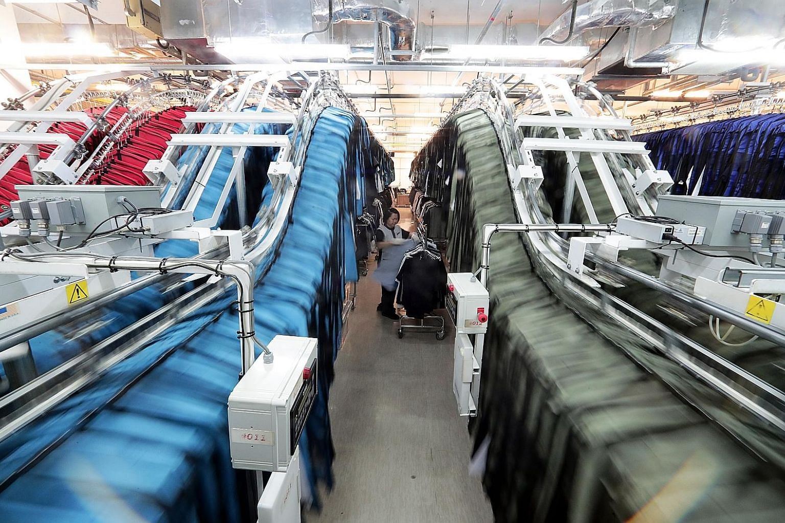 Staff uniforms being loaded onto conveyor belts in Marina Bay Sands' wardrobe room. Some 160,000 uniforms, which can be tracked with sewn-in radio frequency identification tags, are identified and collected by staff in half a minute, with just a swip