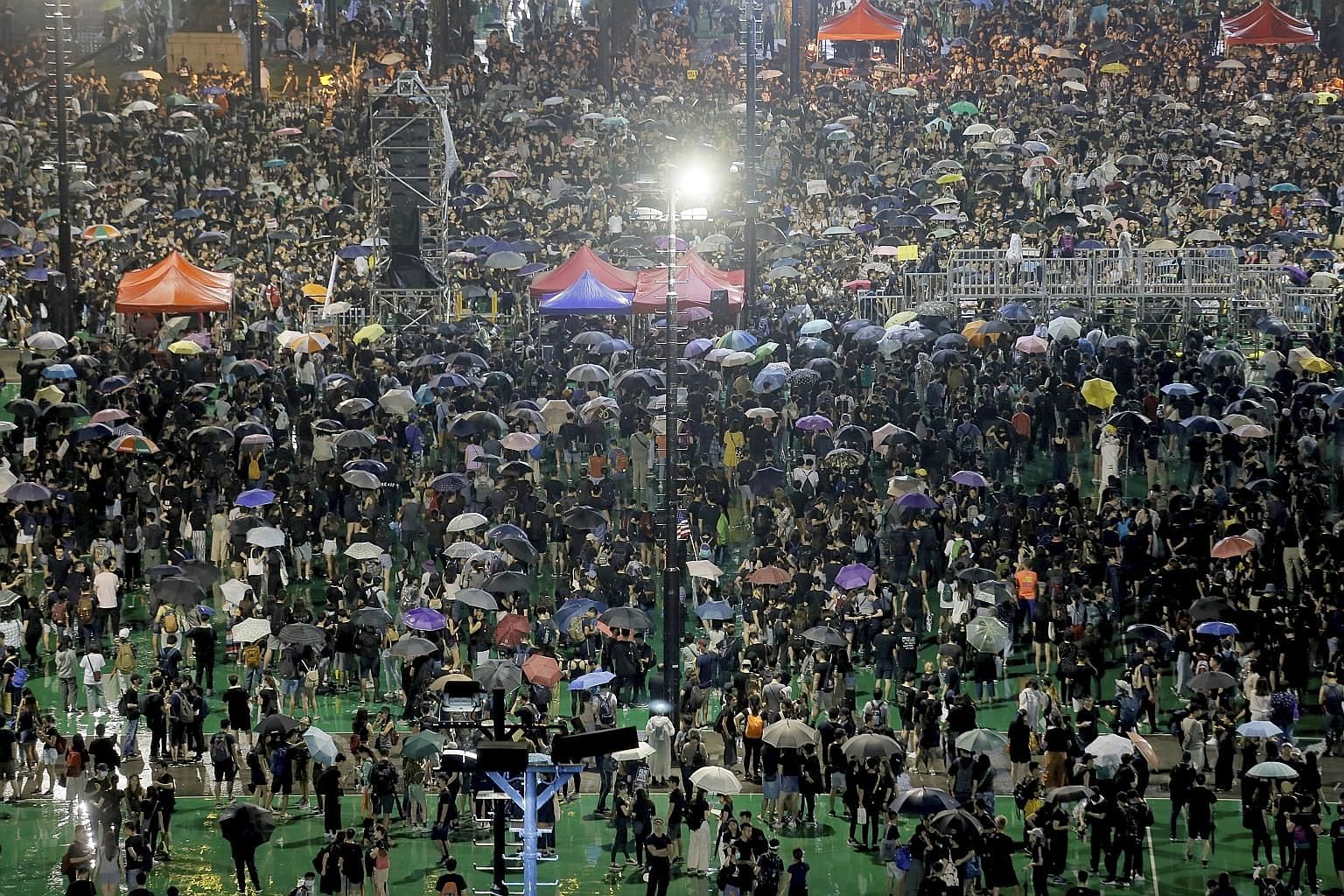 Hong Kong protesters braving the rain at yesterday's rally in Victoria Park. The weekend's protests were the first largely peaceful rallies in 11th straight weekends of demonstrations in the city.
