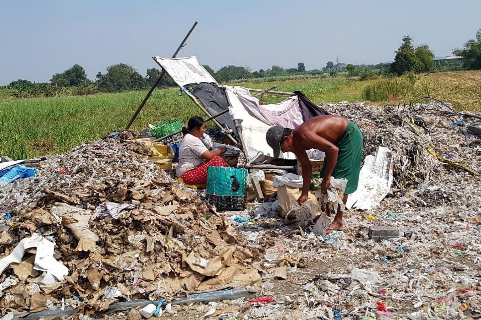 Left: Waste-picker Suparah of Sumengko village in Gresik, East Java, showing trash from a nearby paper factory. She earns about 50,000 rupiah (S$4.90) a day sorting garbage provided by her neighbour. Right: Yanti, a resident of Bangun village in Mojo