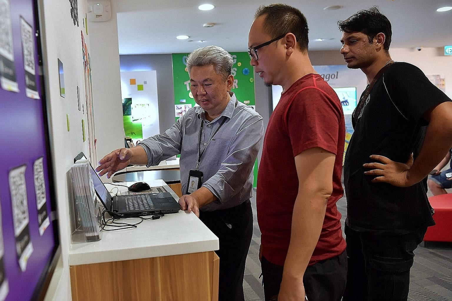 Service ambassador Ng Thiam Hock (left), 60, guides customers through electronic transactions and attends to their inquiries at the HDB Punggol branch office. Having upskilled to take on different roles, he is among the first batch of public officers