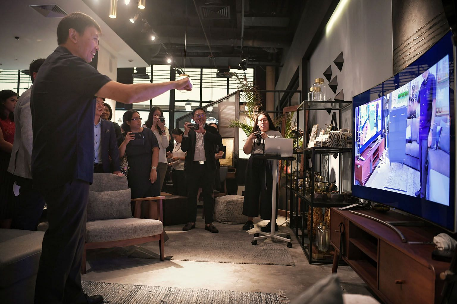 Senior Minister of State for Trade and Industry Chee Hong Tat trying out augmented reality technology on his visit to furniture store Commune at Millenia Walk yesterday.