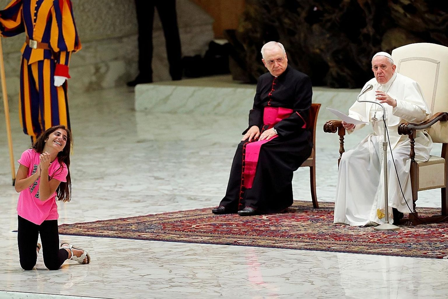 The girl pranced back and forth in front of Pope Francis, jumped, and occasionally let go a loud, sharp clap, as he led the weekly general audience in Paul VI Hall at the Vatican yesterday. Pope Francis signalled to security to let her be. The girl r