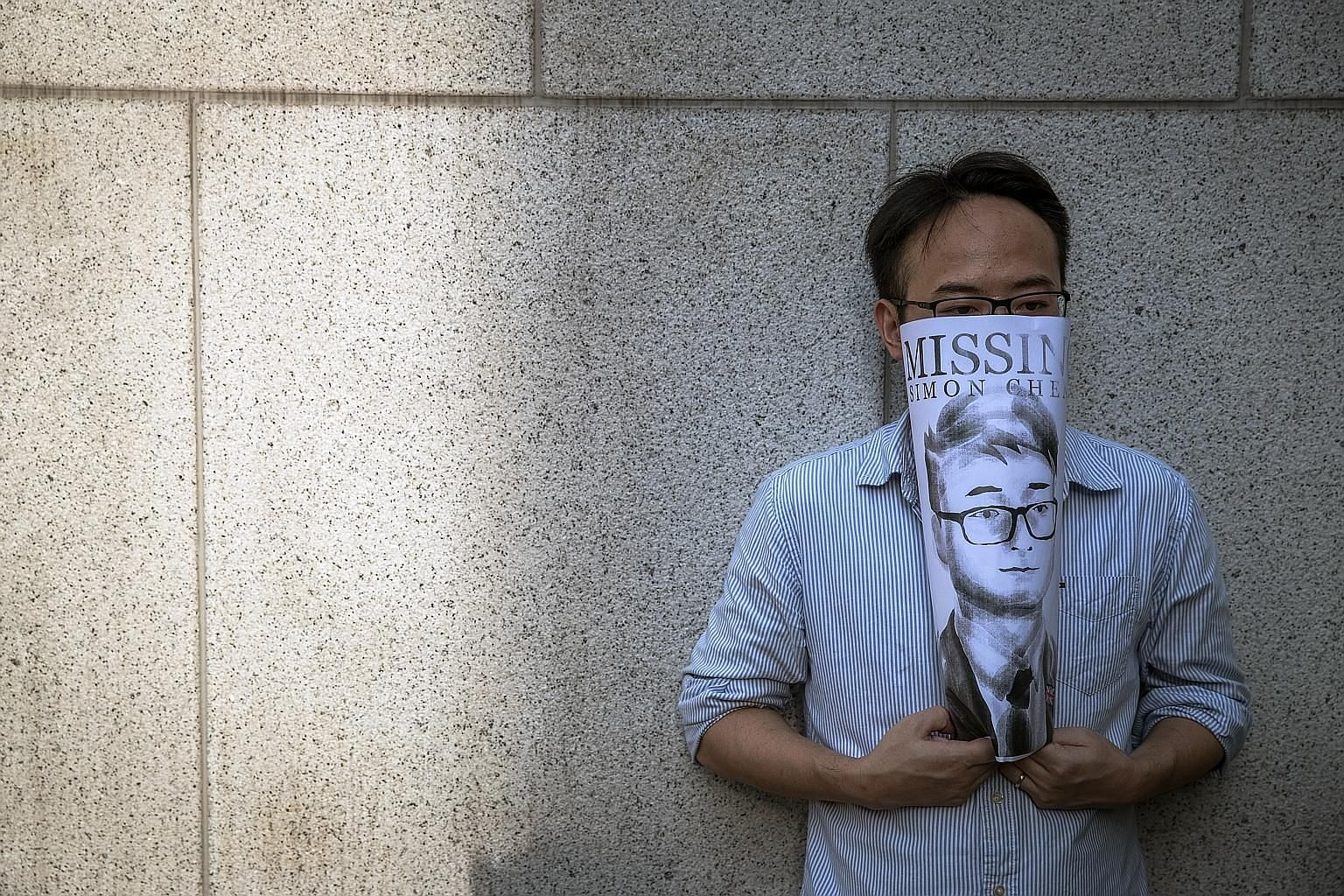 An activist holding an illustration of Mr Simon Cheng at a rally outside the British consulate in Hong Kong on Wednesday. The UK Foreign Office said neither it nor Mr Cheng's family has been able to speak to him since his detention. PHOTO: EPA-EFE