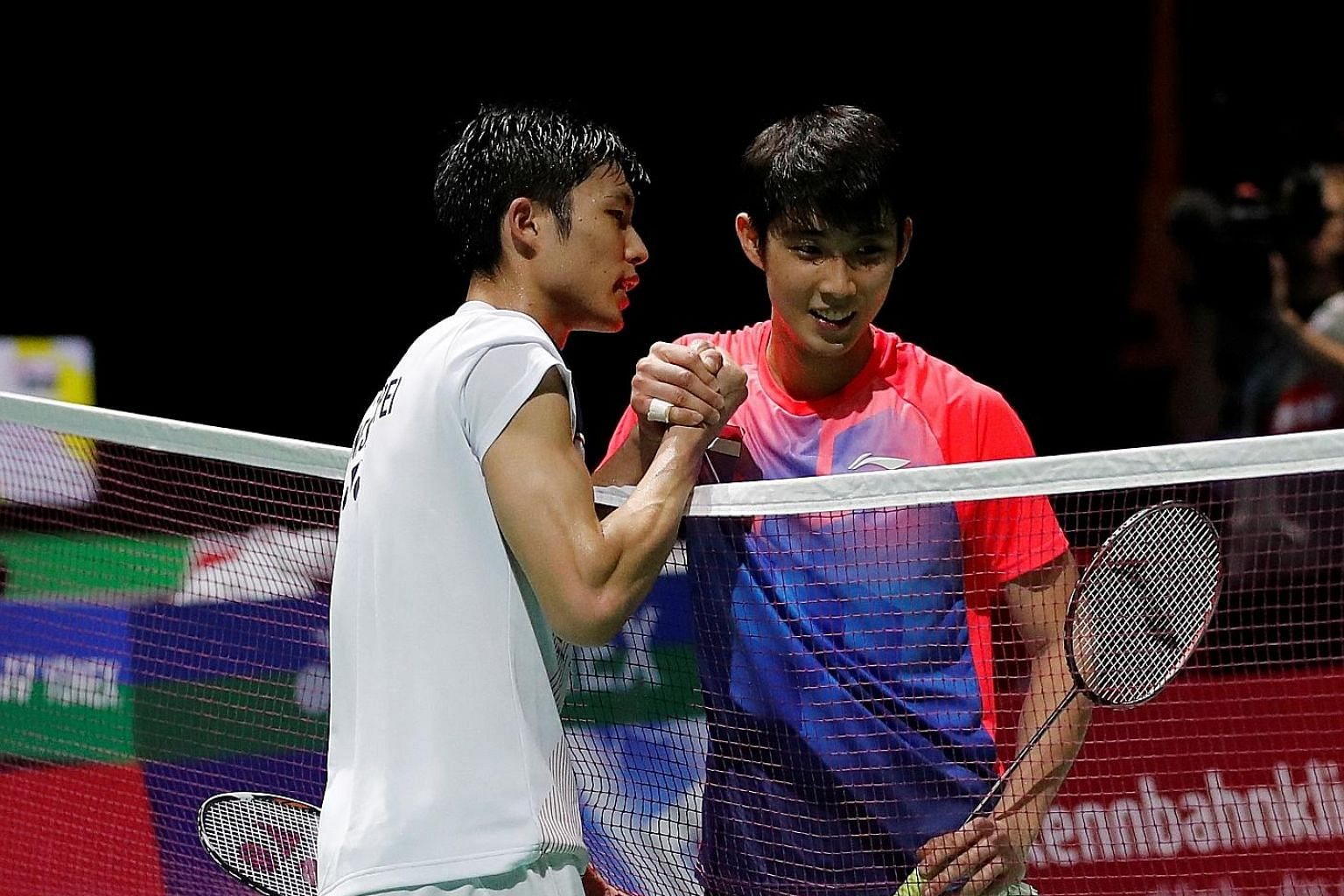 Chinese Taipei's Chou Tien-chen consoling Loh Kean Yew (right) at the net after beating the Singaporean in the third round of the BWF World Championships in Basel yesterday. While he exited the tournament, Yeo Jia Min (above) will play Thailand's Rat