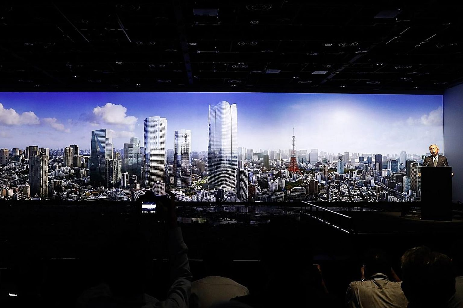 Mori Building CEO Shingo Tsuji announcing the Toranomon-Azabudai project, which is slated for completion in March 2023. An artist's impression of the project's three new buildings can be seen in the background. PHOTO: MORI BUILDING
