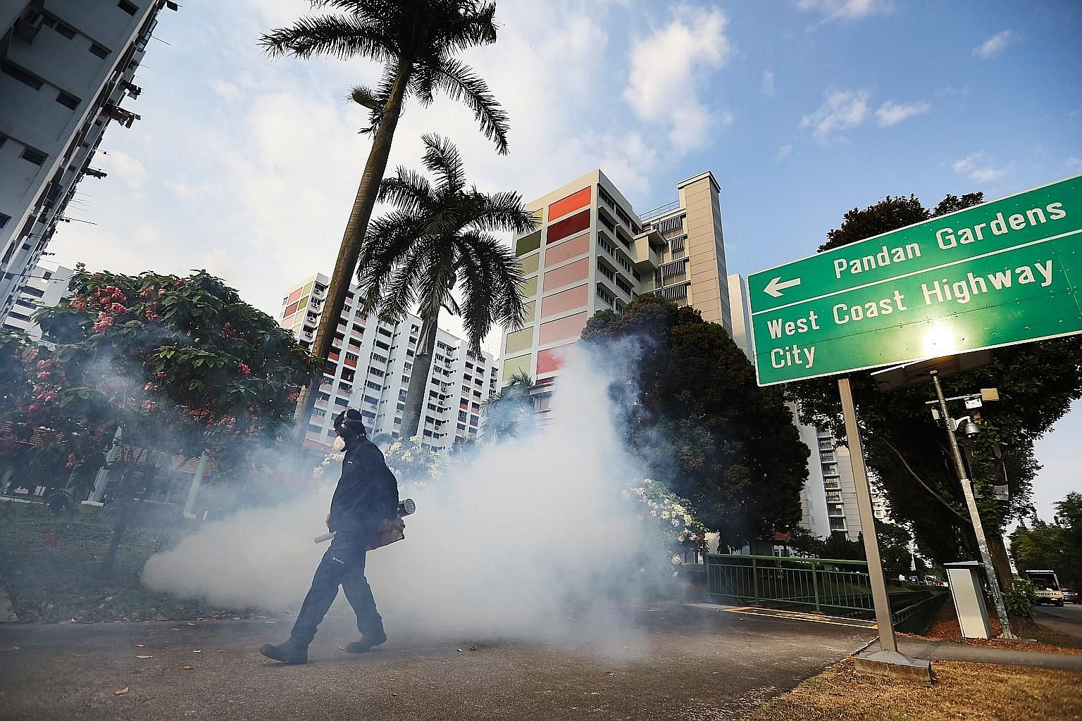 A PUB contractor carrying out fogging at Housing Board blocks near Pandan Reservoir earlier this month.
