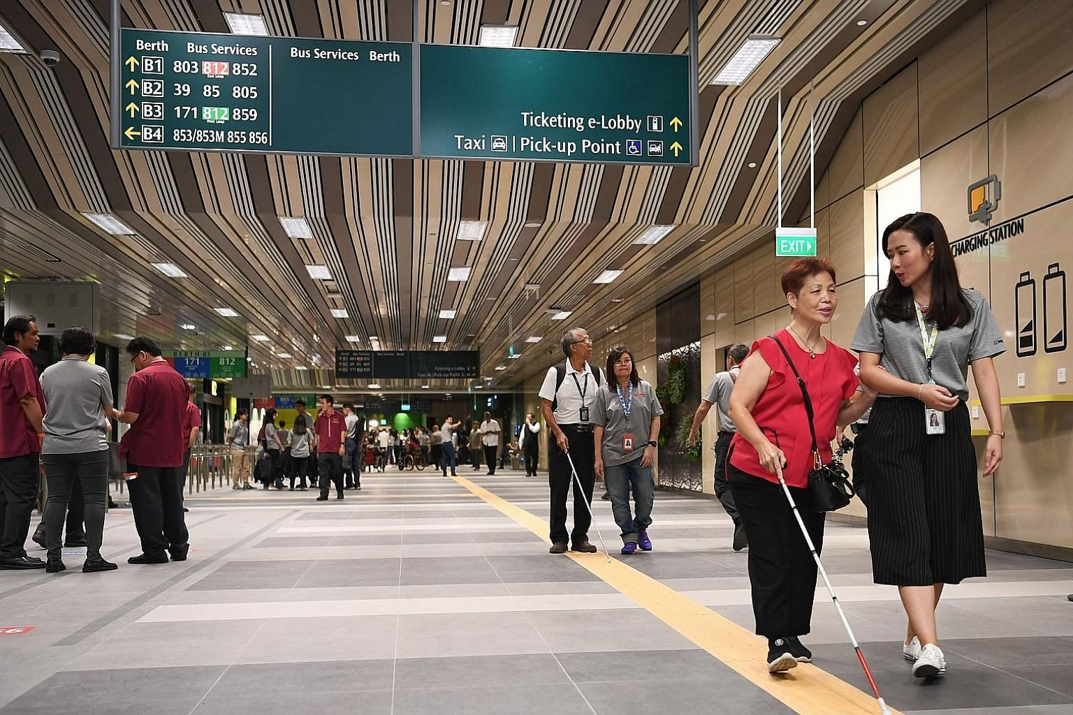 People with visual impairment being guided by SMRT staff yesterday in a tour of the Yishun Integrated Transport Hub, which will open next month. The hub is also a place where the public can take commuters with dementia; trained staff will then attend