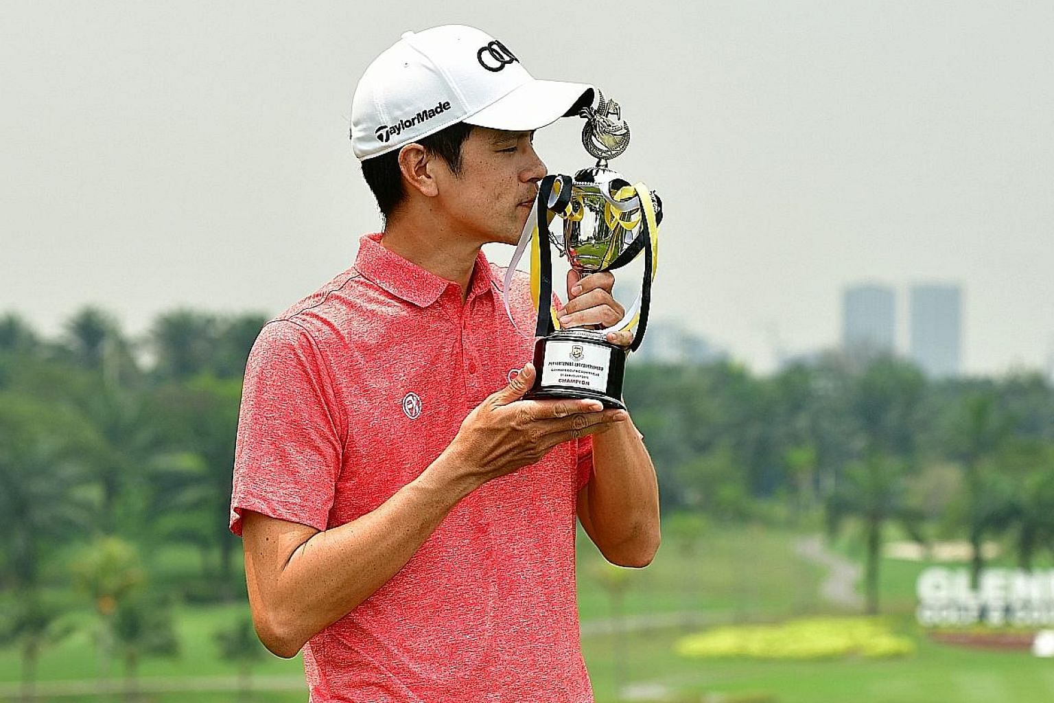 Singaporean golfer Quincy Quek kissing the PGM Northport ADT Championship trophy after coming from three shots behind to beat overnight leader Adam Blyth by one in Kuala Lumpur yesterday.