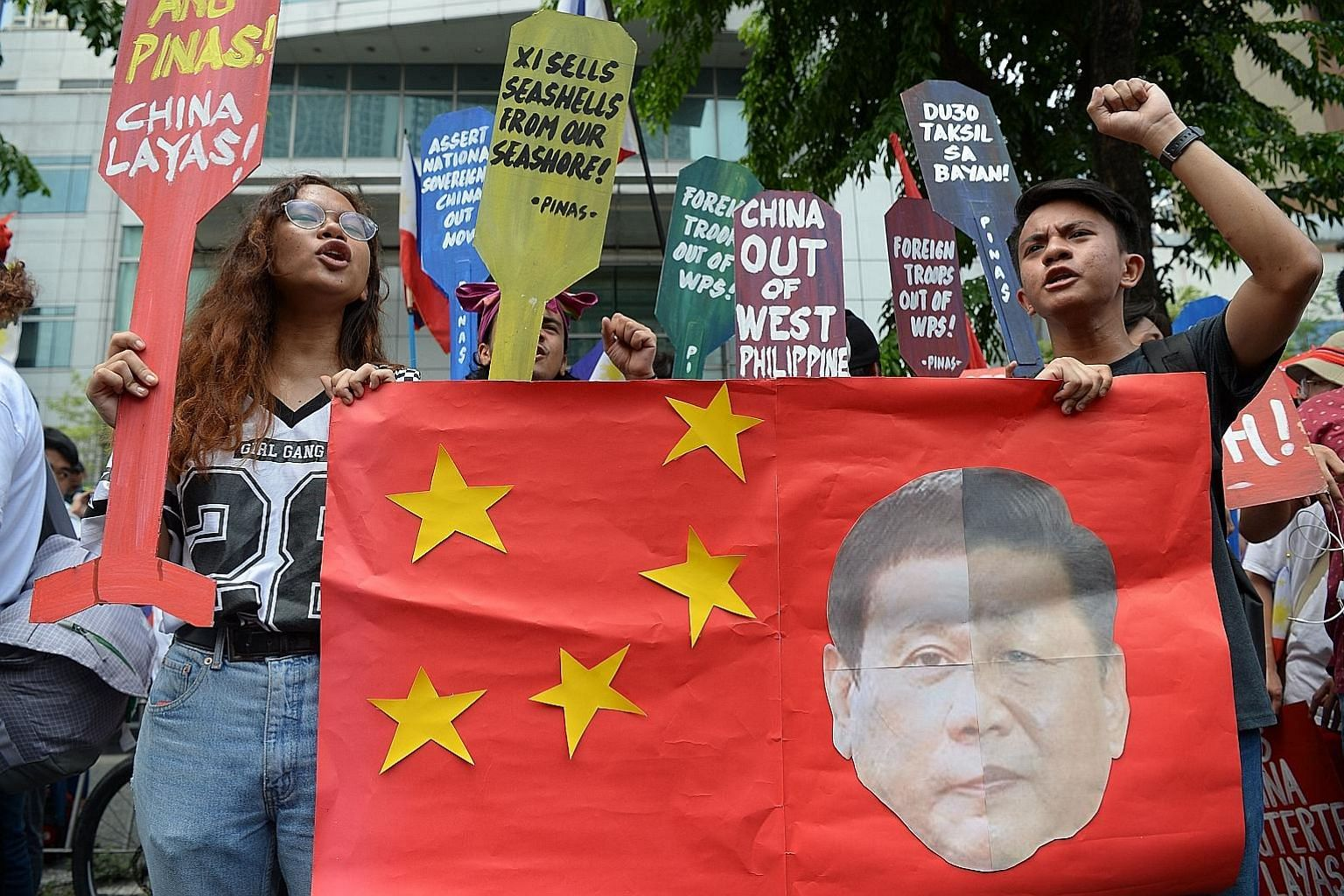 Protesters holding placards and shouting anti-China slogans during a rally in front of the Chinese consulate in Manila last month. They were opposing the Asian superpower's growing sway in the Philippines, as tensions rise over Beijing's presence in