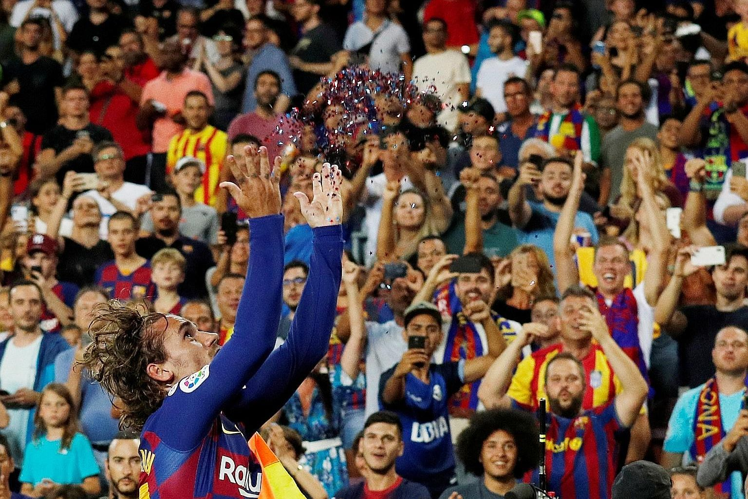 Barcelona forward Antoine Griezmann throwing glitter in the air before spreading his arms LeBron James-style to celebrate his second goal in the 5-2 rout of Real Betis on Sunday. PHOTO: REUTERS