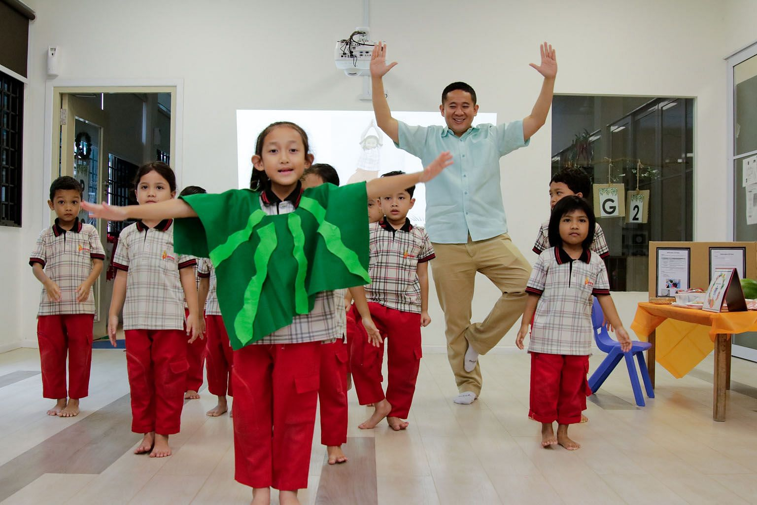 Senior Parliamentary Secretary for Health and Home Affairs, Mr Amrin Amin, with pre-school children in a yoga session at the Singapore Muslim Women's Association (PPIS) Child Development Centre in Bukit Batok yesterday. Apart from teaching the childr