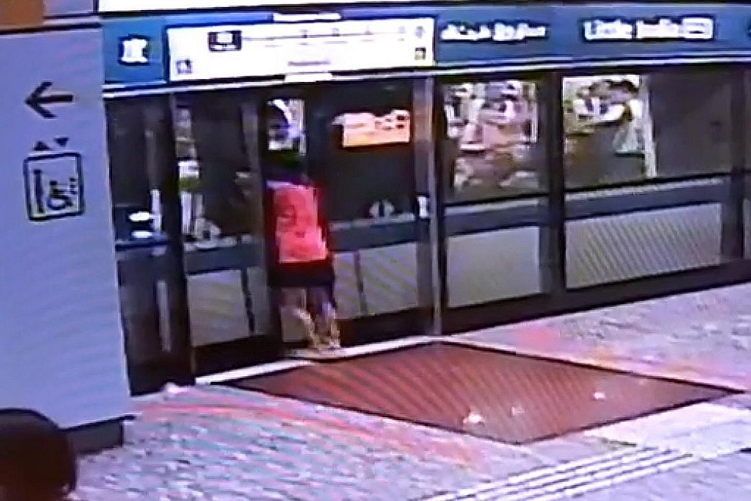 In a screen grab of a video shared on social media, a woman is seen prising open the platform doors before attempting to force open the train doors. The clip also shows commuters trying to help her.