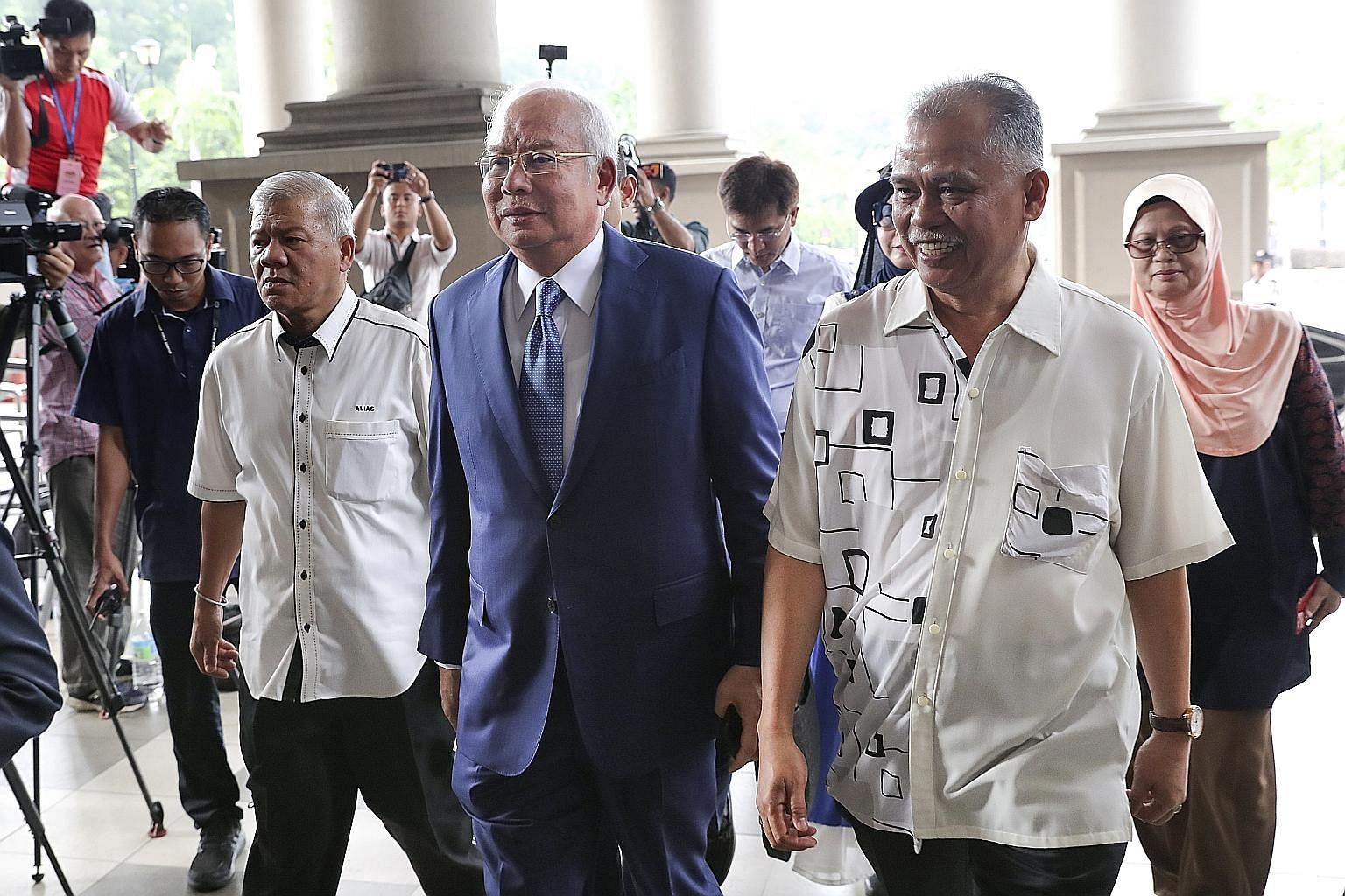 Former prime minister Najib Razak arriving with supporters at Kuala Lumpur High Court for his 1MDB trial yesterday. He faces 21 counts of money laundering and four counts of abuse of power for receiving illegal transfers totalling RM2.28 billion (S$7