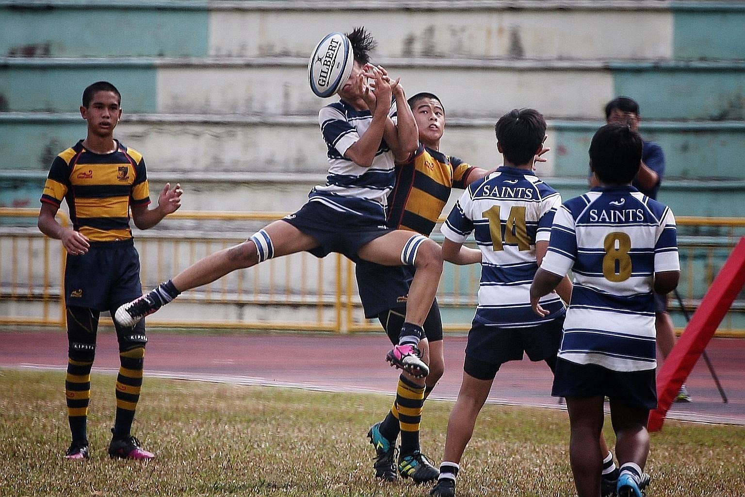 Players from St Andrew's Secondary School (in blue and white) and Anglo-Chinese School (Independent) compete in the C Division rugby final. ST PHOTO: JASON QUAH