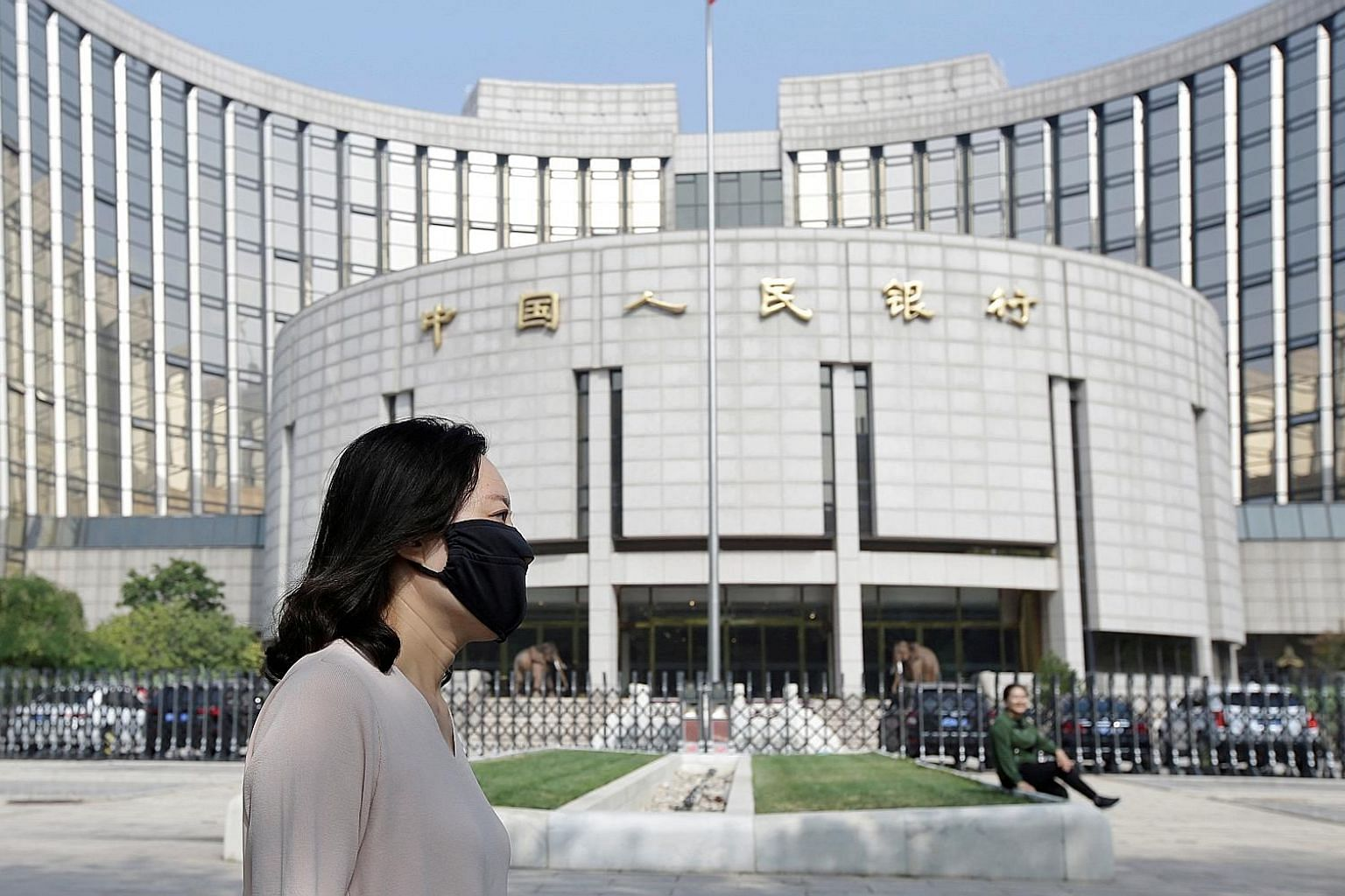 Despite efforts by China's central bank, the People's Bank of China (left), to stabilise the yuan via daily fixing, the currency is on track for 11 straight sessions of losses against the US dollar. PHOTO: REUTERS