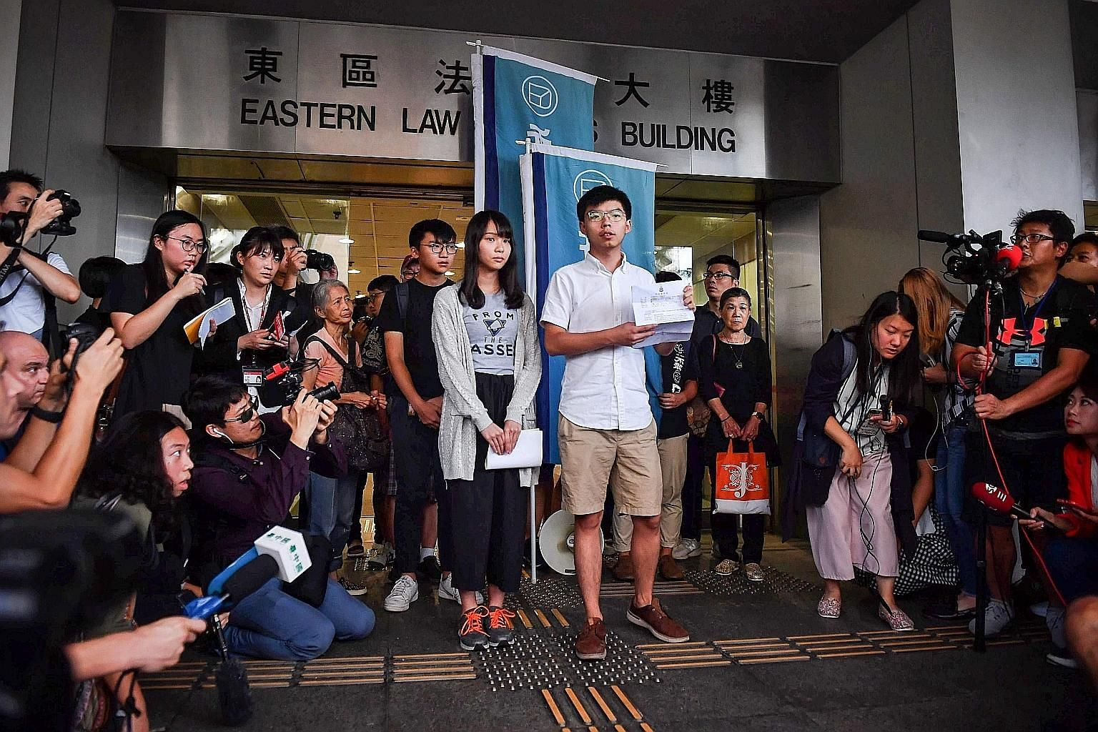 Demosisto party's leader Joshua Wong and member Agnes Chow speaking to the press yesterday at the Wan Chai police headquarters after being released on bail. They are accused of taking part in a June 21 unauthorised demonstration outside Wan Chai poli
