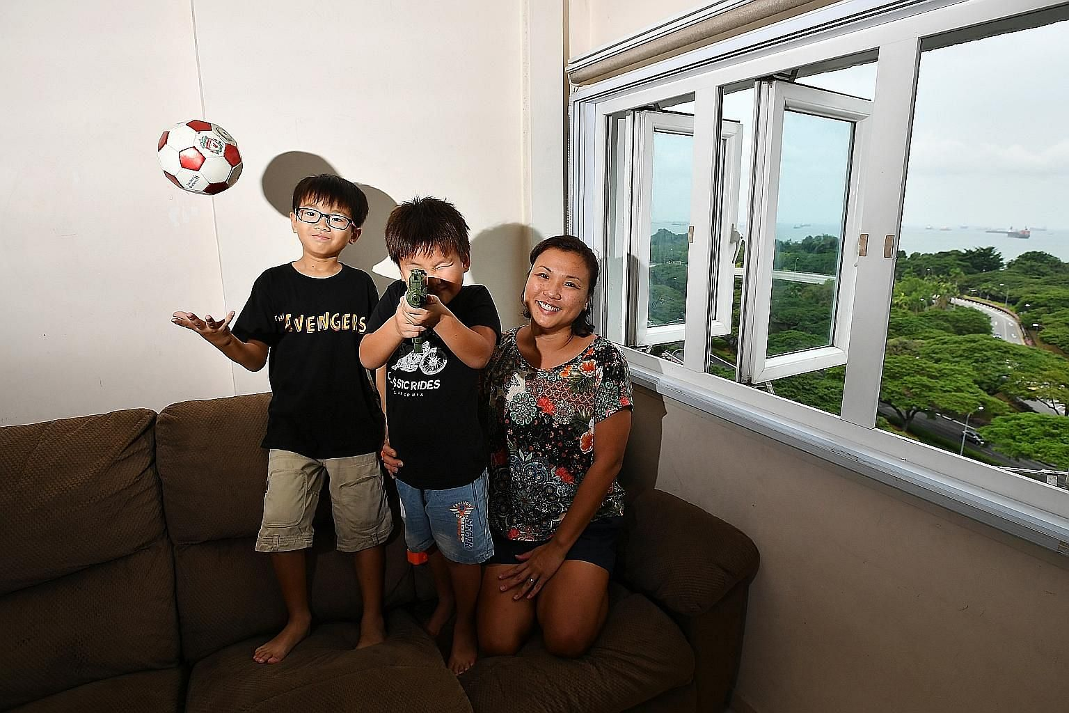 Housewife Heather Ho, 41, with two of her three children, 10-year-old Elliot Tan (with glasses) and Nathanael Tan, five, in their Marine Drive five-room HDB flat. Her parents bought it for around $35,000 in 1978 and transferred ownership of this flat