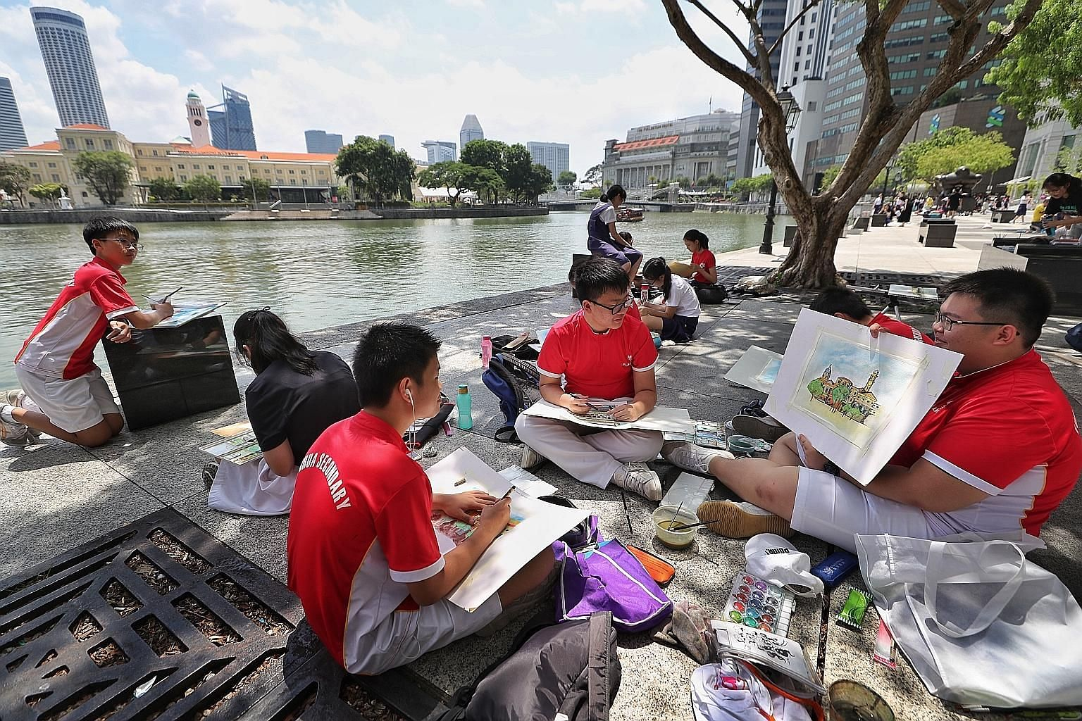 Fuhua Secondary School student Donovan Dua, 14, showing schoolmates Zou Muyan (centre), 15, and Kwa Jun Hao, 14, his painting of buildings around the Singapore River.