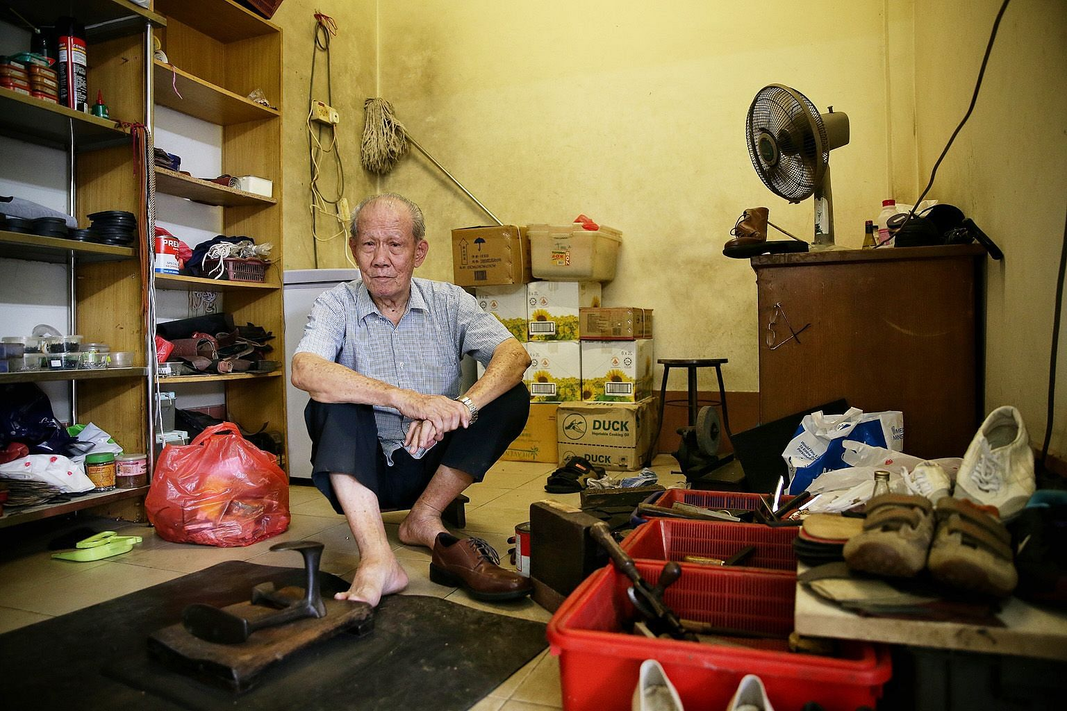 """Mr Low Poh Lye at his shoe repair shop in Bukit Timah Market and Food Centre. The octogenarian still works each morning """"to pass the time, have some fun"""", even though he does not need the income."""