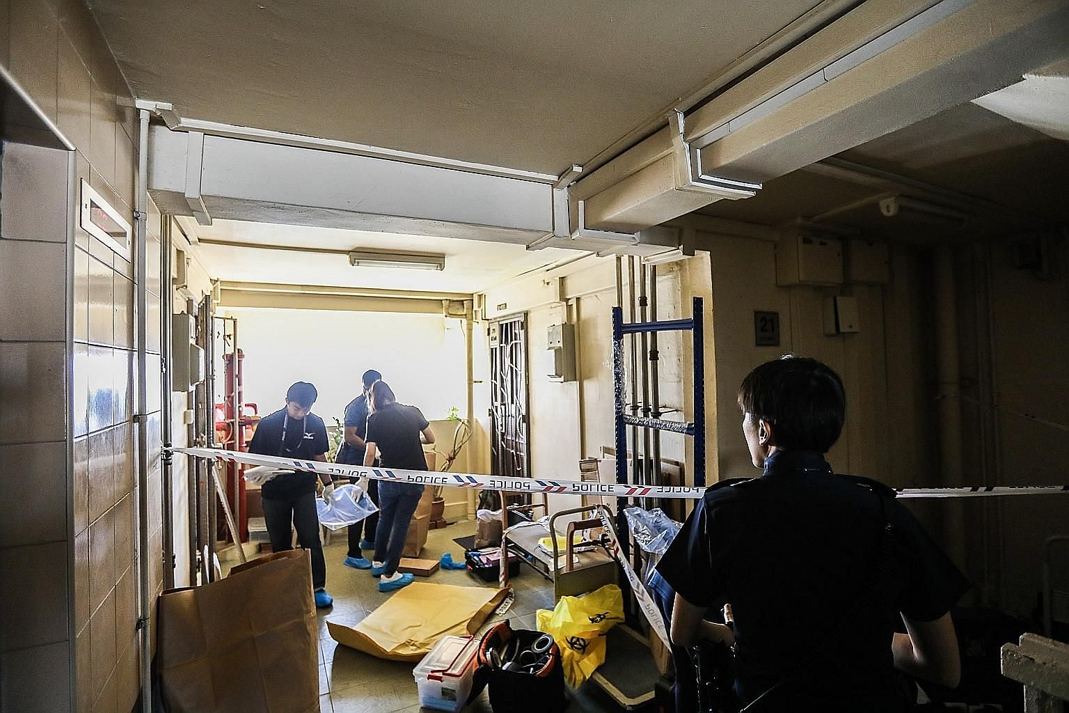 Police officers gathering evidence from inside the unit at Block 191 Lorong 4 Toa Payoh yesterday morning.
