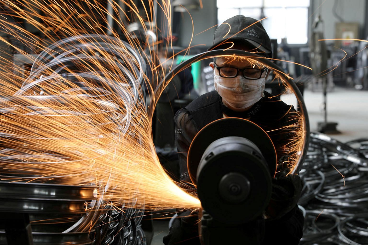 A worker welding a bicycle steel rim at a factory manufacturing sports equipment in Hangzhou, Zhejiang province. In handling both its internal and external problems, China, unlike the US, at least appears to have a playbook, says the writer. It is no